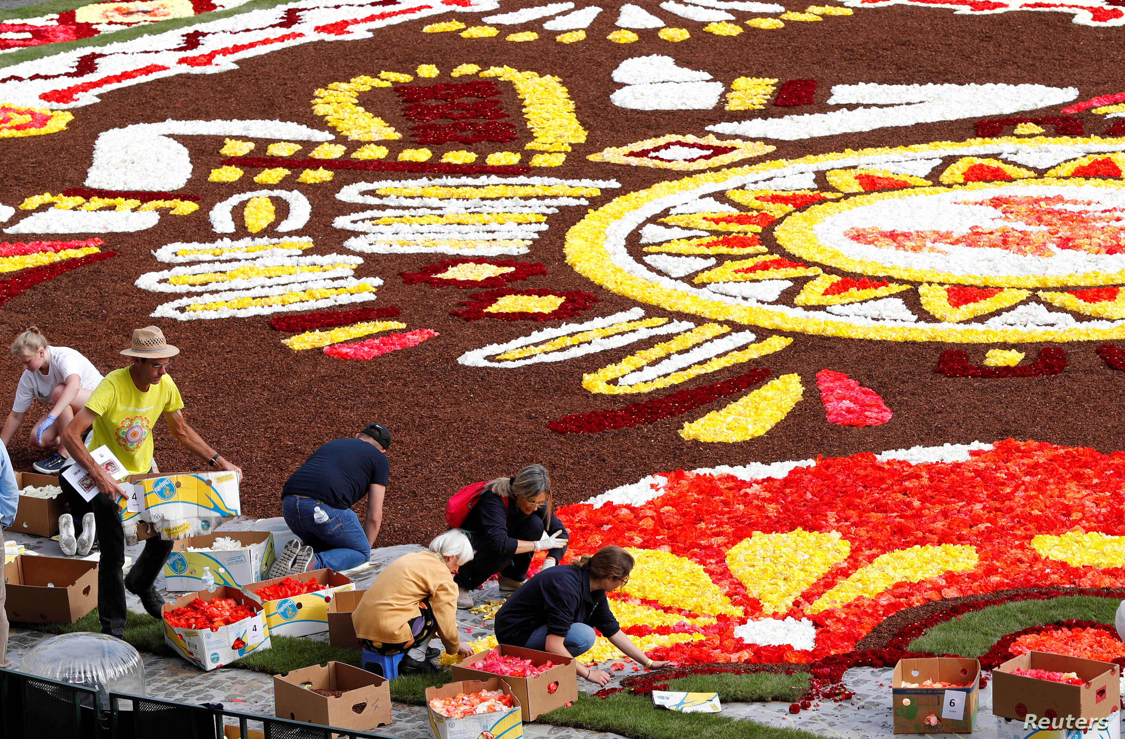 Gardeners adjust flowers on a 1,800-square-meter flower carpet at Brussels' Grand Place, Belgium, Aug. 16, 2018.