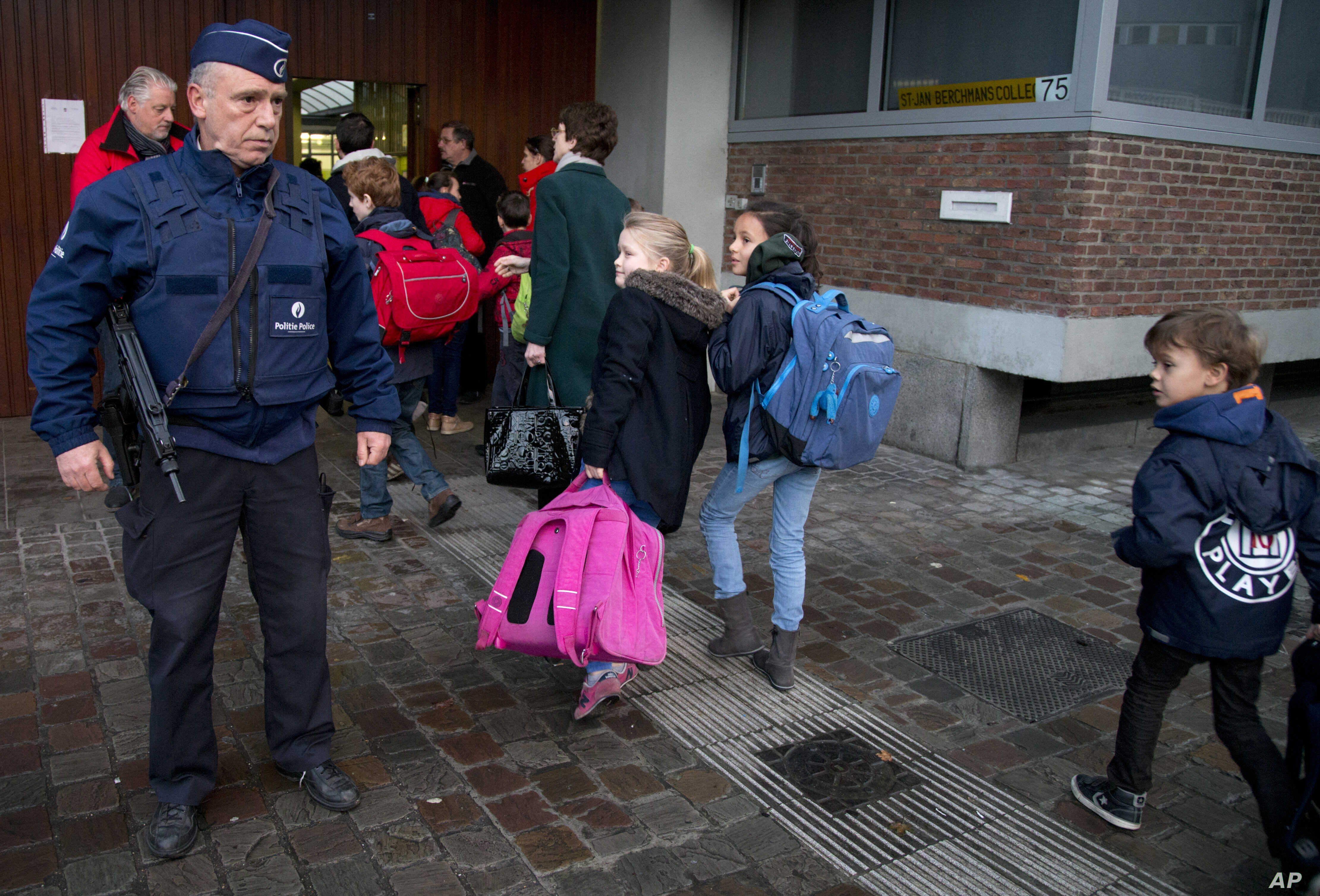 Children pass a police officer as they arrive for school in the center of Brussels, Nov. 25, 2015.