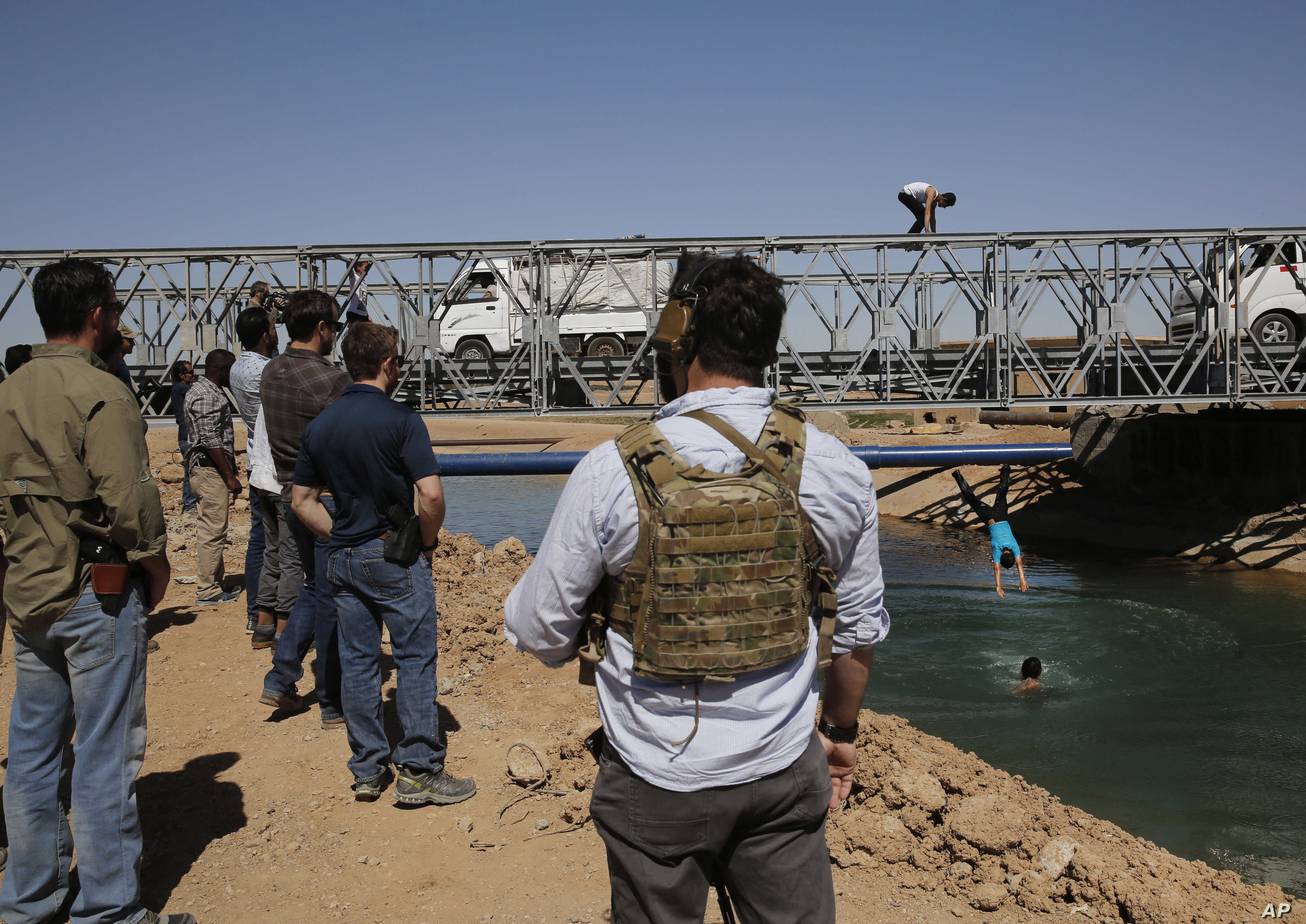 U.S. soldiers in civilian clothes, foreground, watch boys diving into a canal from a newly opened bridge, which had been destroyed last summer during fighting between U.S.-backed Syrian Democratic Forces fighters and Islamic State militants, in Raqqa...