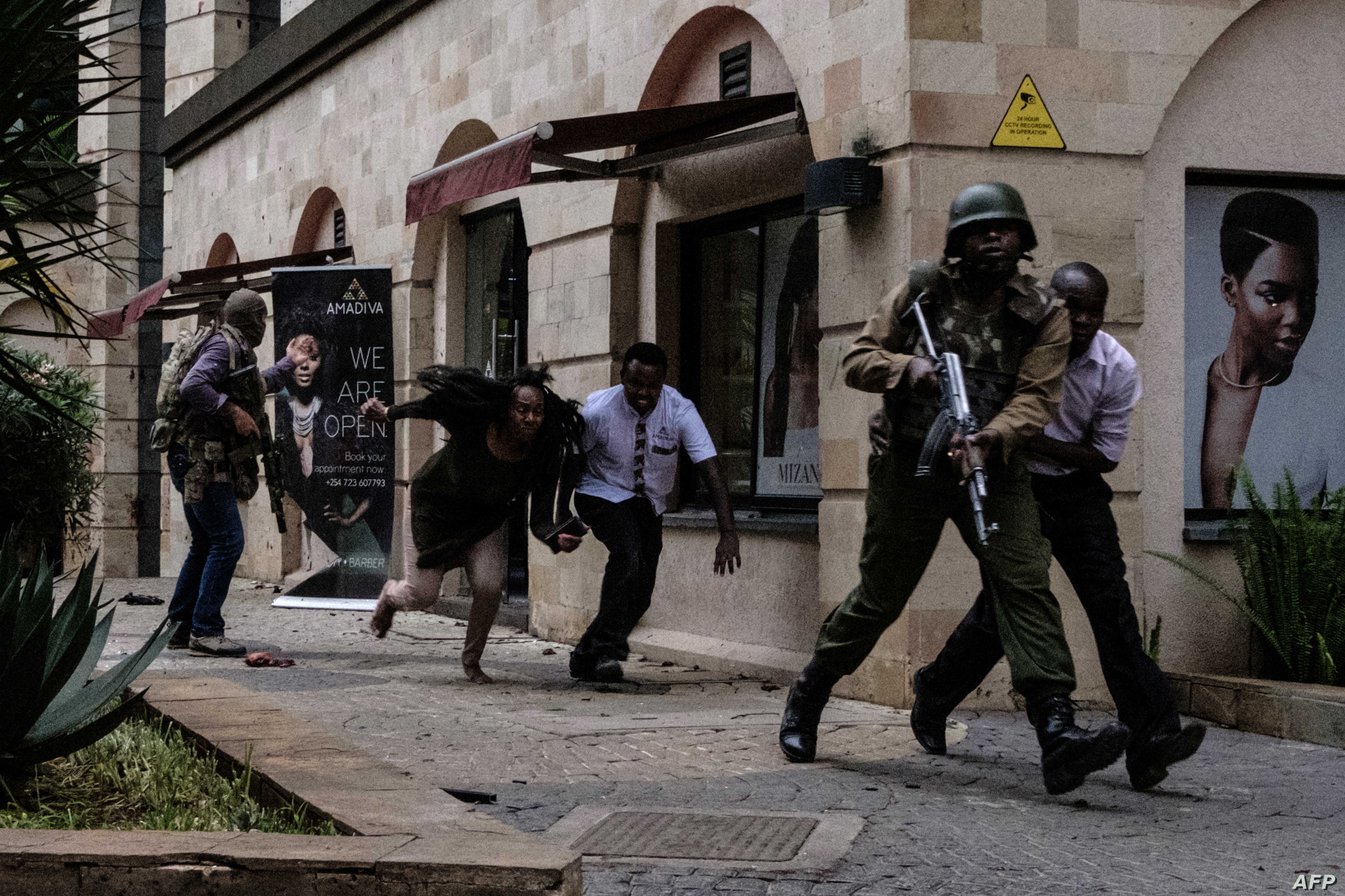 Kenyan security forces help people to escape after a bomb blast at DusitD2 hotel in Nairobi, Kenya, Jan. 15, 2019. A huge blast followed by a gun battle rocked an upmarket hotel and office complex in Nairobi, causing casualties, in an attack claimed ...