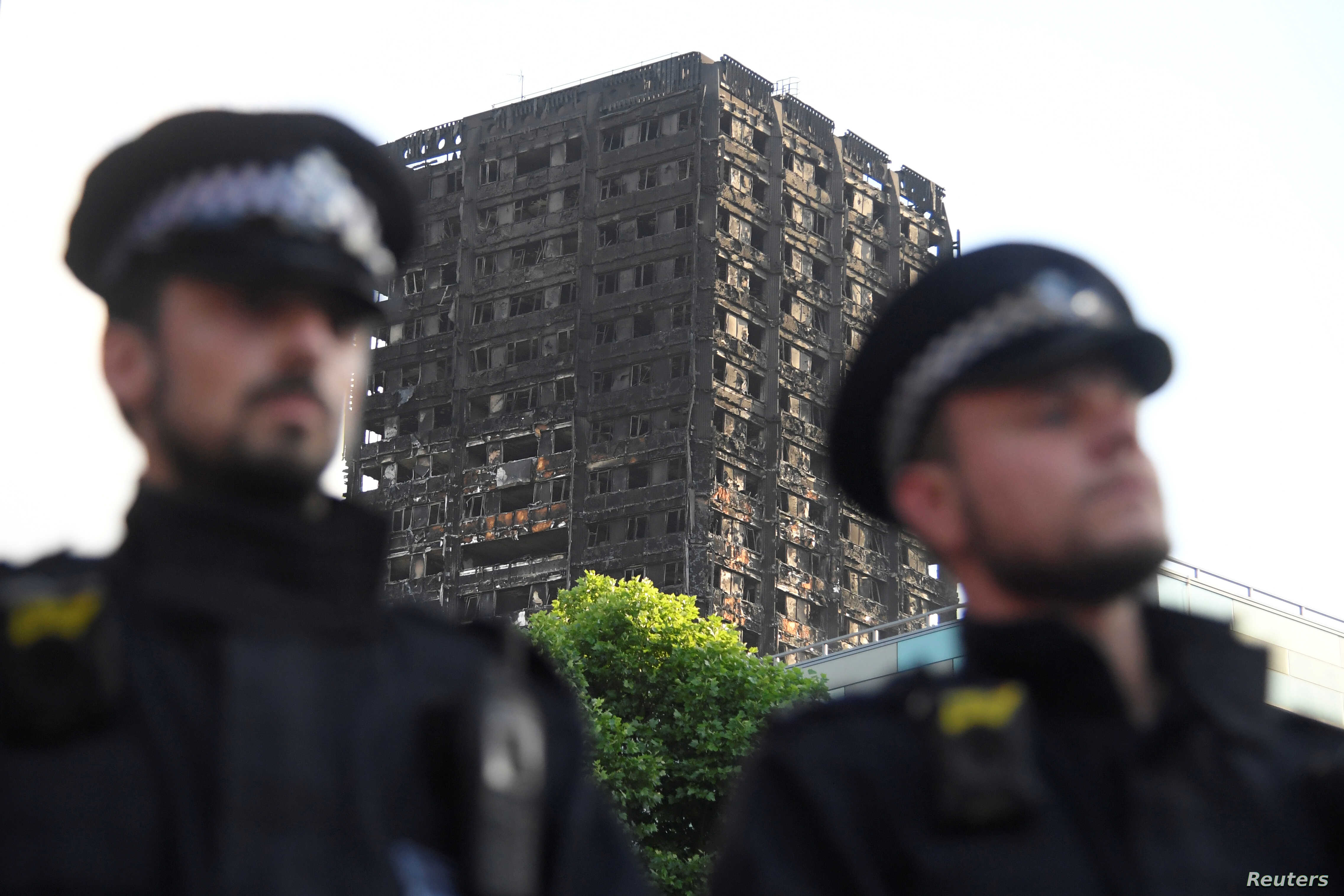 Police officers stand in front of the The Grenfell Tower block that was destroyed by fire, in north Kensington, West London, Britain, June 16, 2017.