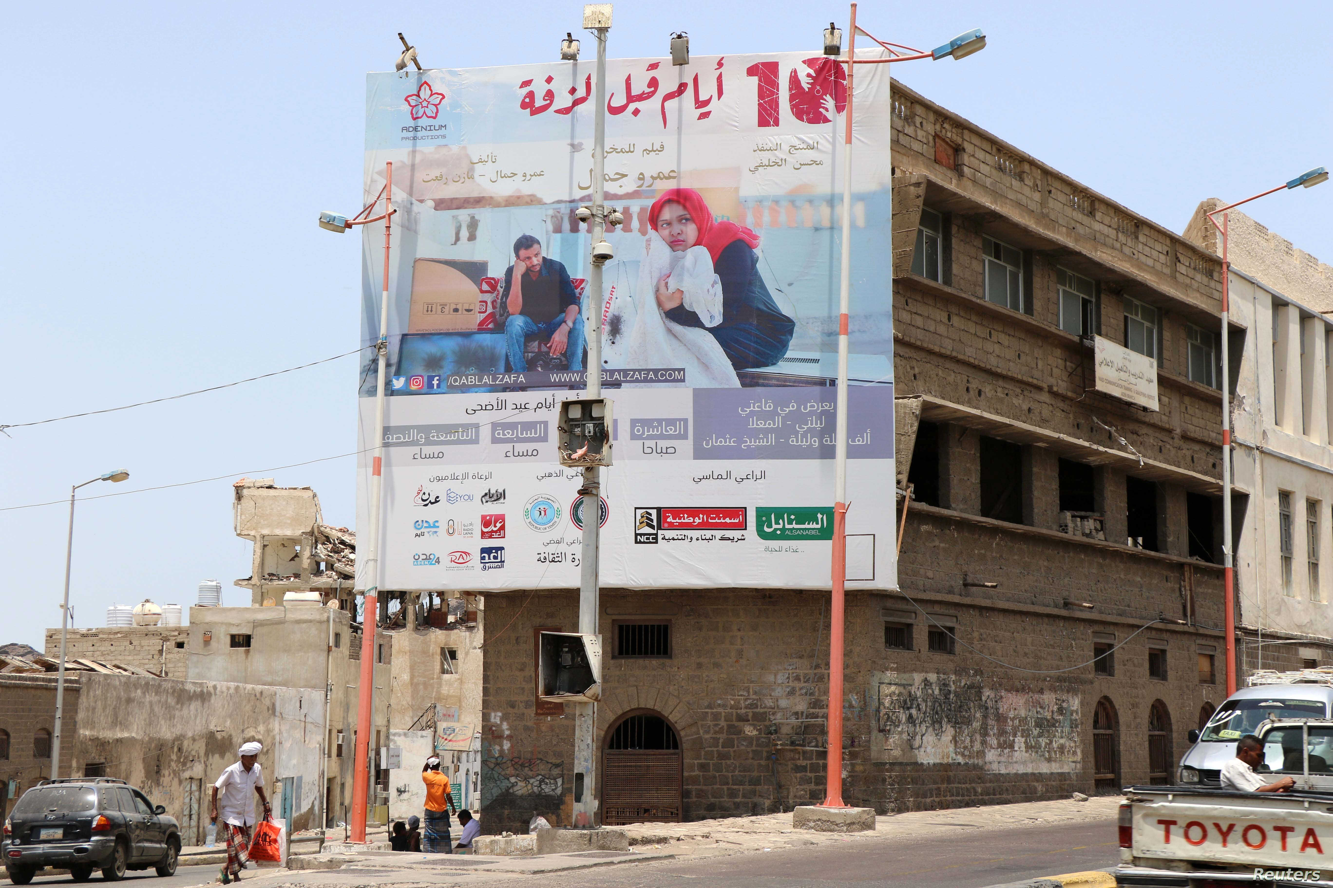 """A man walks past a billboard displaying an advertisement for the local movie """"10 Days Before the Wedding"""" in Aden, Yemen, Sept. 1, 2018."""