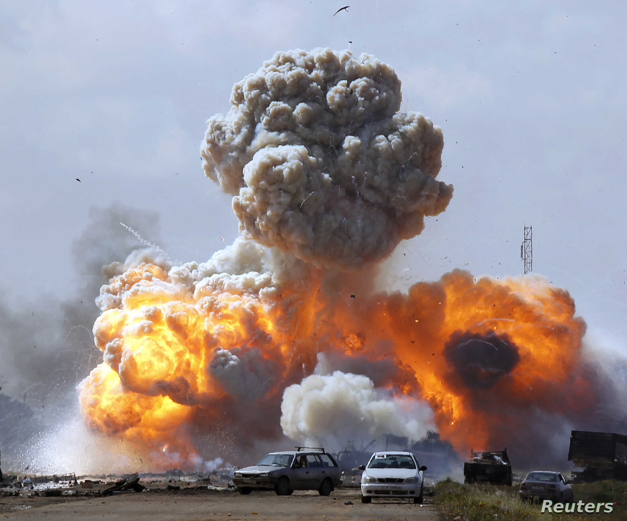 Vehicles belonging to forces loyal to Libyan leader Moammar Gadhafi explode after an airstrike by coalition forces, along a road between Benghazi and, March 20, 2011.