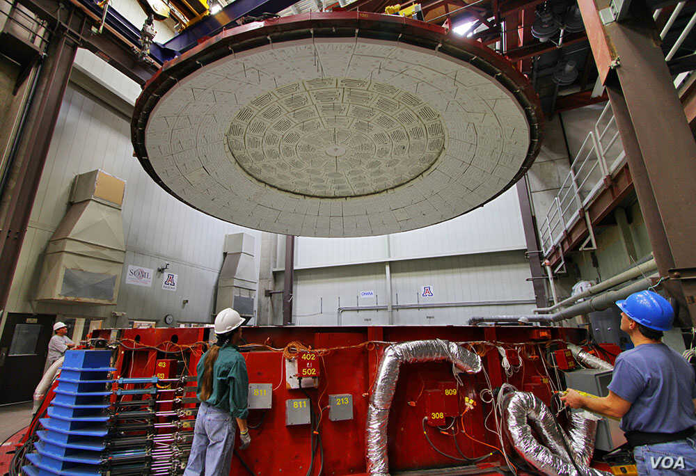 Workers at Steward Observatory Mirror Lab prepare the rotating furnance in which the GMT mirror was cast. (Steward Observatory Mirror Lab/University of Arizona)