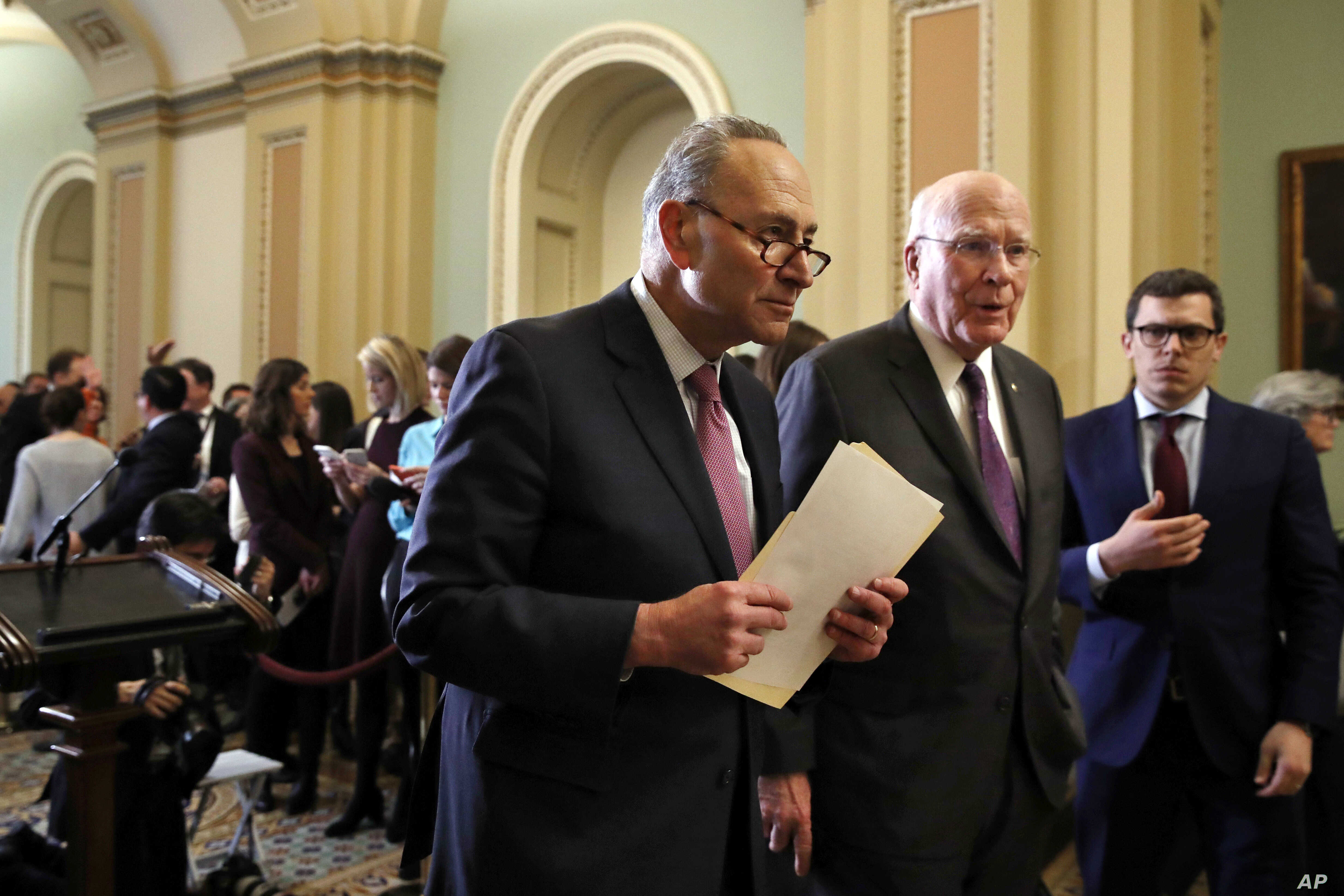 Senate Minority Leader Sen. Chuck Schumer of New York, center, walks with Sen. Patrick Leahy, D-Vt., right, as they leave a news conference with Democratic leaders, March 20, 2018, on Capitol Hill in Washington.