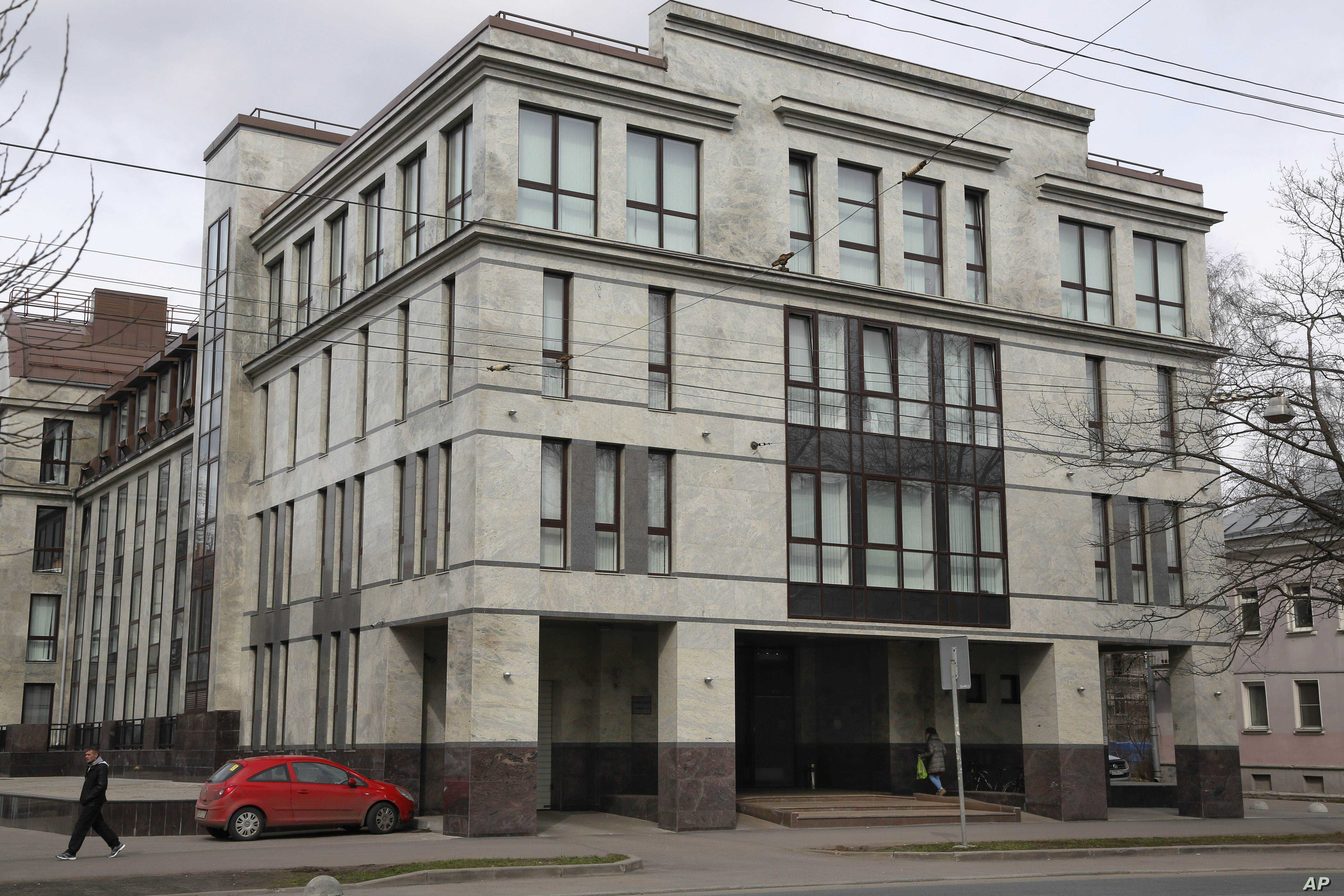 """FILE - In this picture taken April 19, 2015,  a women enters the four-story building known as the """"troll factory""""  in St. Petersburg, Russia. The """"troll factory"""" is where hundreds of young Russians work around the clock writing blogs and posting ..."""