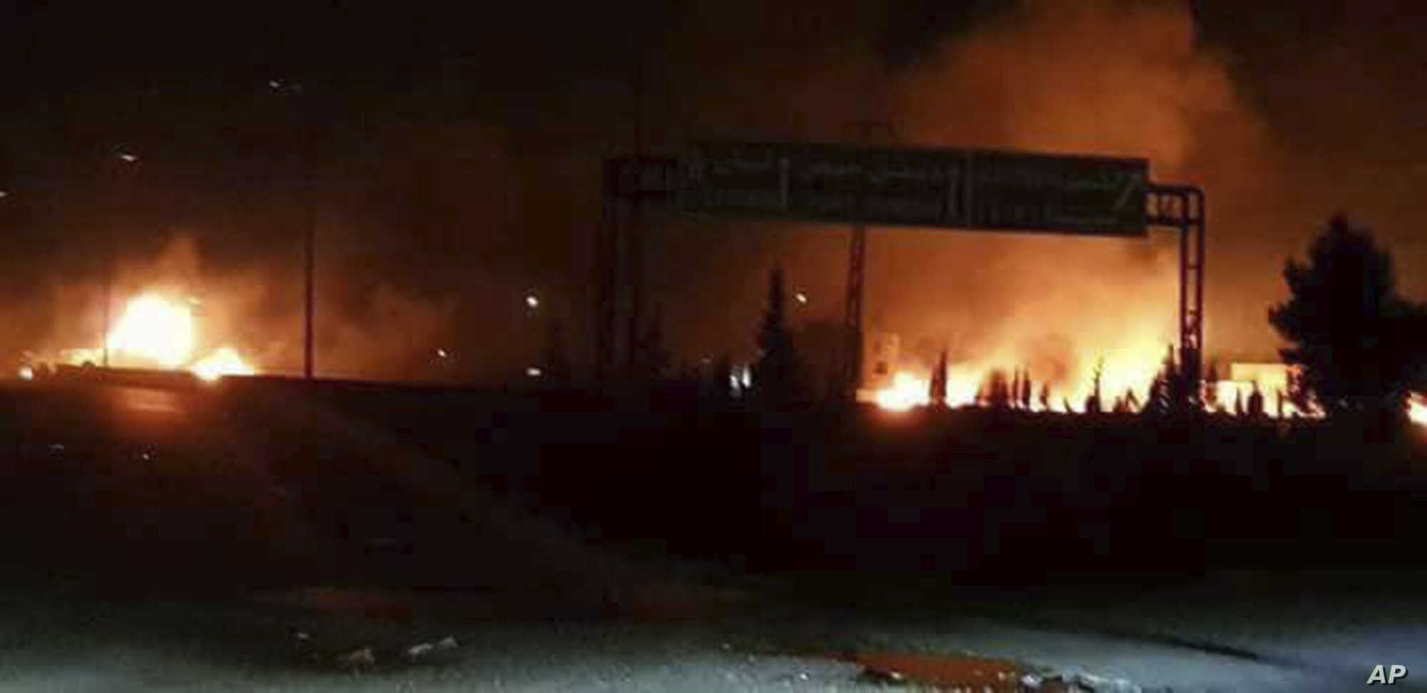 This photo released on Wednesday, May 9, 2018, by the Syrian official news agency SANA, shows flames rising after an attack in an area known to have numerous Syrian army military bases, in Kisweh, south of Damascus, Syria.