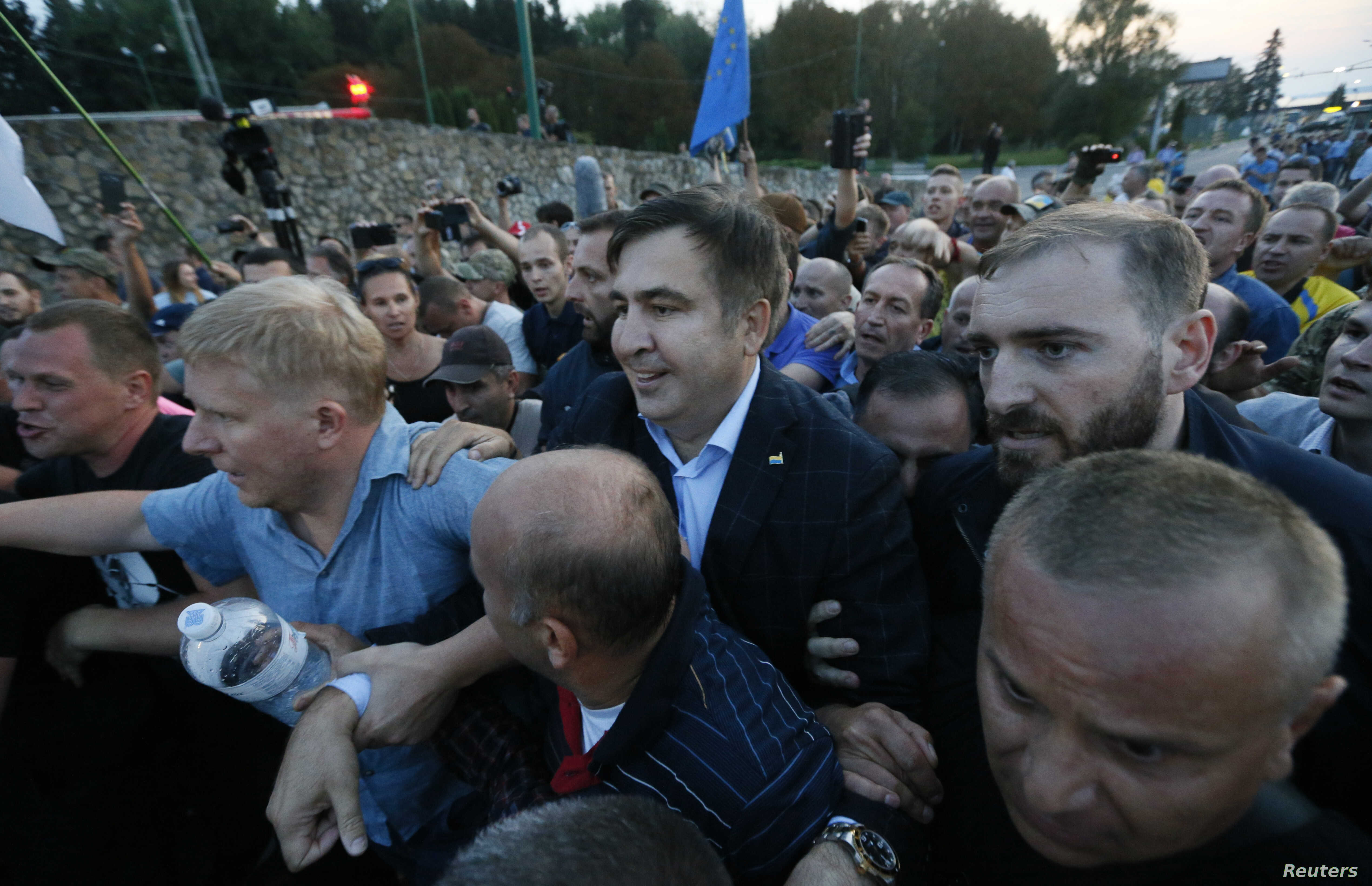 Former Georgian President Mikheil Saakashvili is surrounded by his supporters as he arrives at a checkpoint on the Ukrainian-Polish border in Shehyni, Ukraine, Sept. 10, 2017.