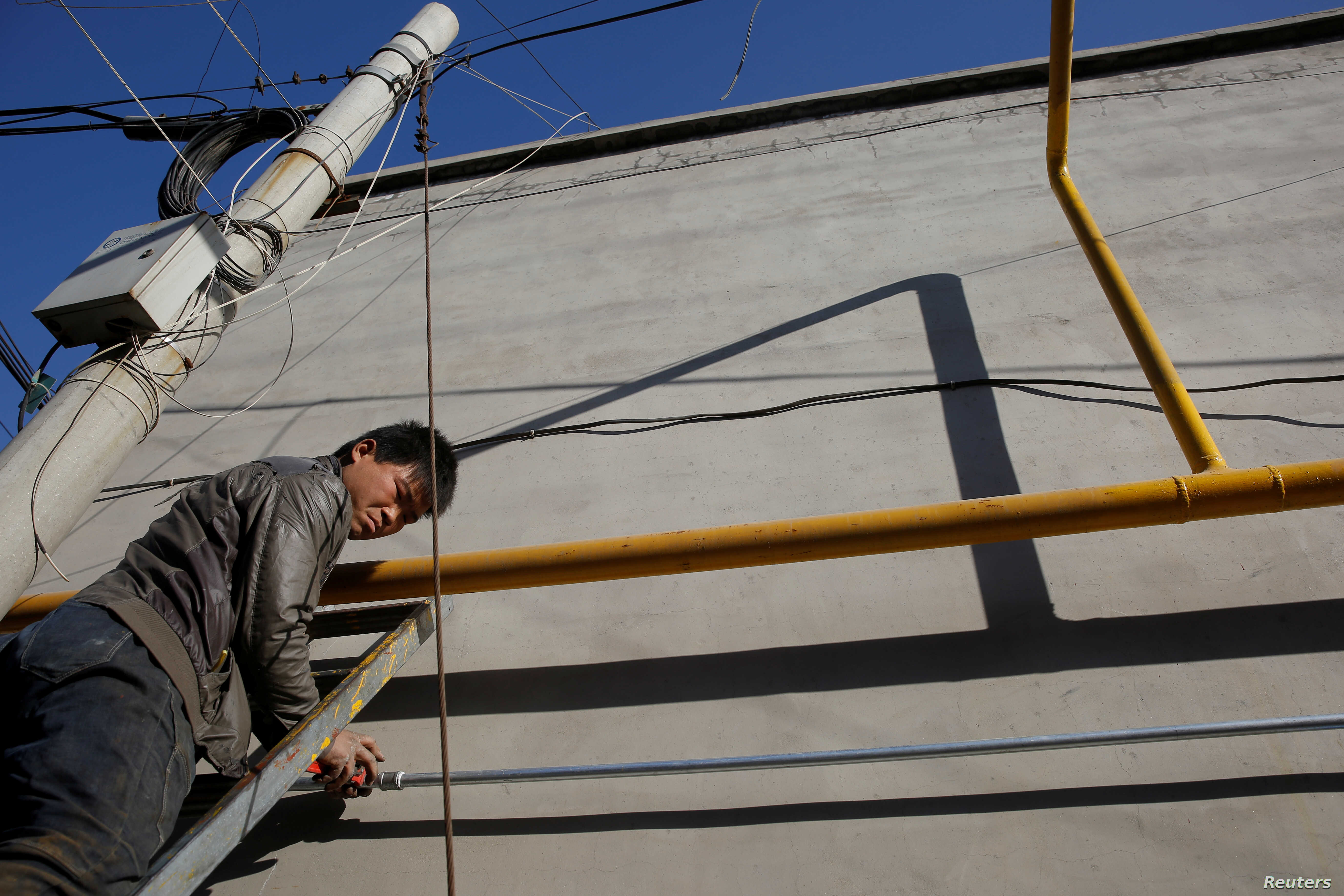 A worker installs gas pipes along the walls of residential houses in the village of Heqiaoxiang outside of Baoding, Hebei province, China, Dec. 5, 2017.