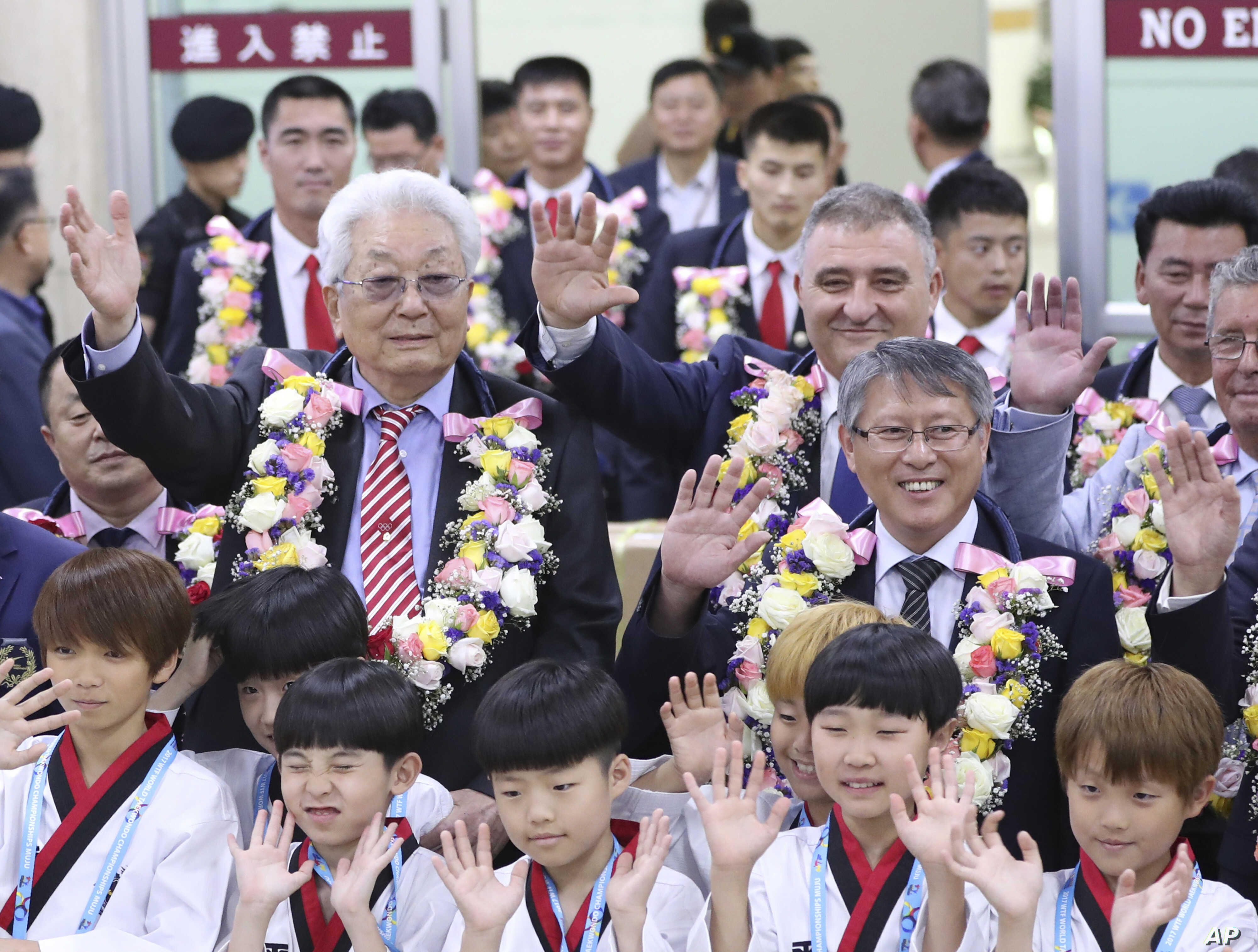 North Korea's IOC member Chang Ung, middle row left, waves with officials of International Taekwondo Federation upon their arrival at Gimpo International Airport in Seoul, South Korea, June 23, 2017.