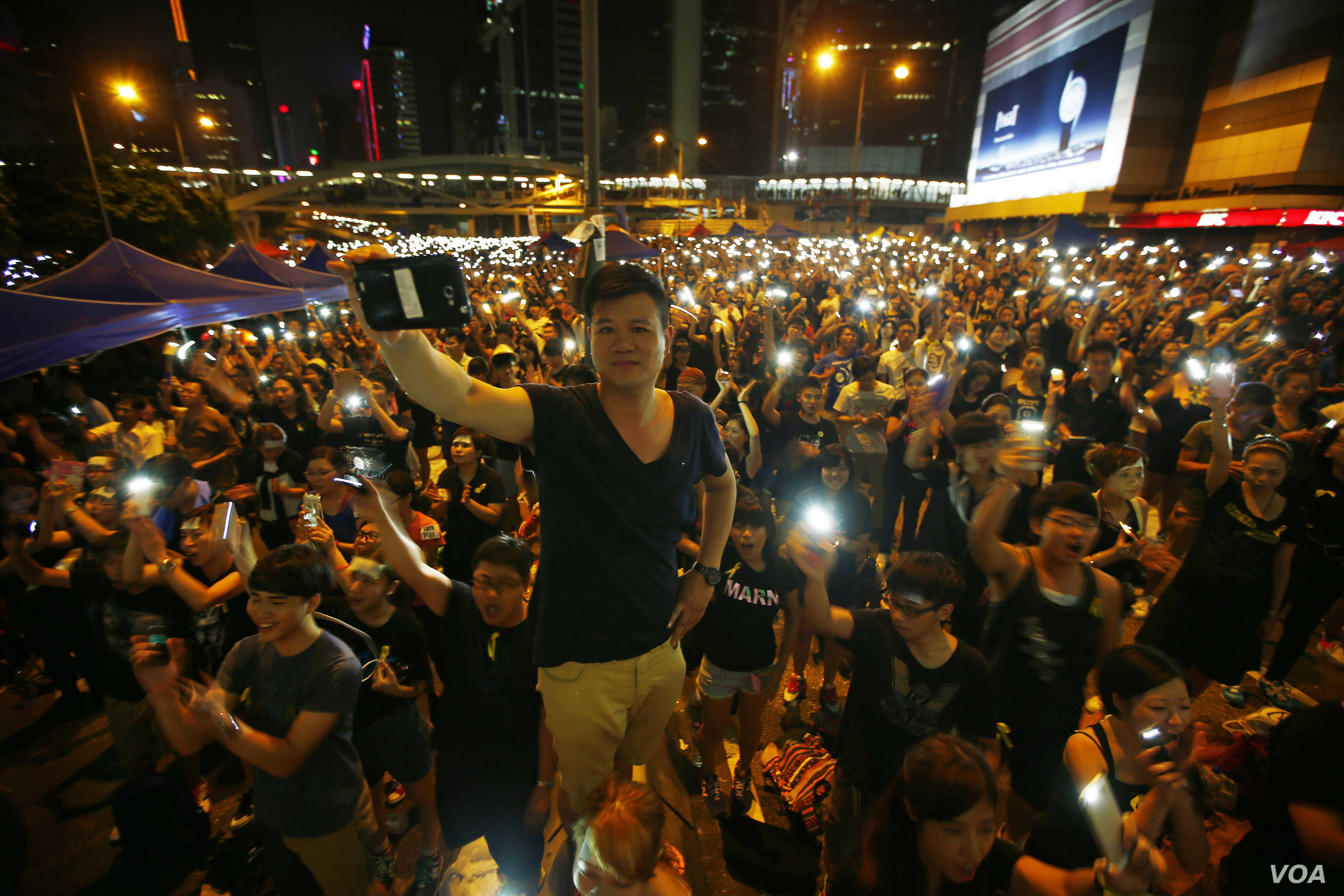 Protesters turn on their mobile phone flashlights as they