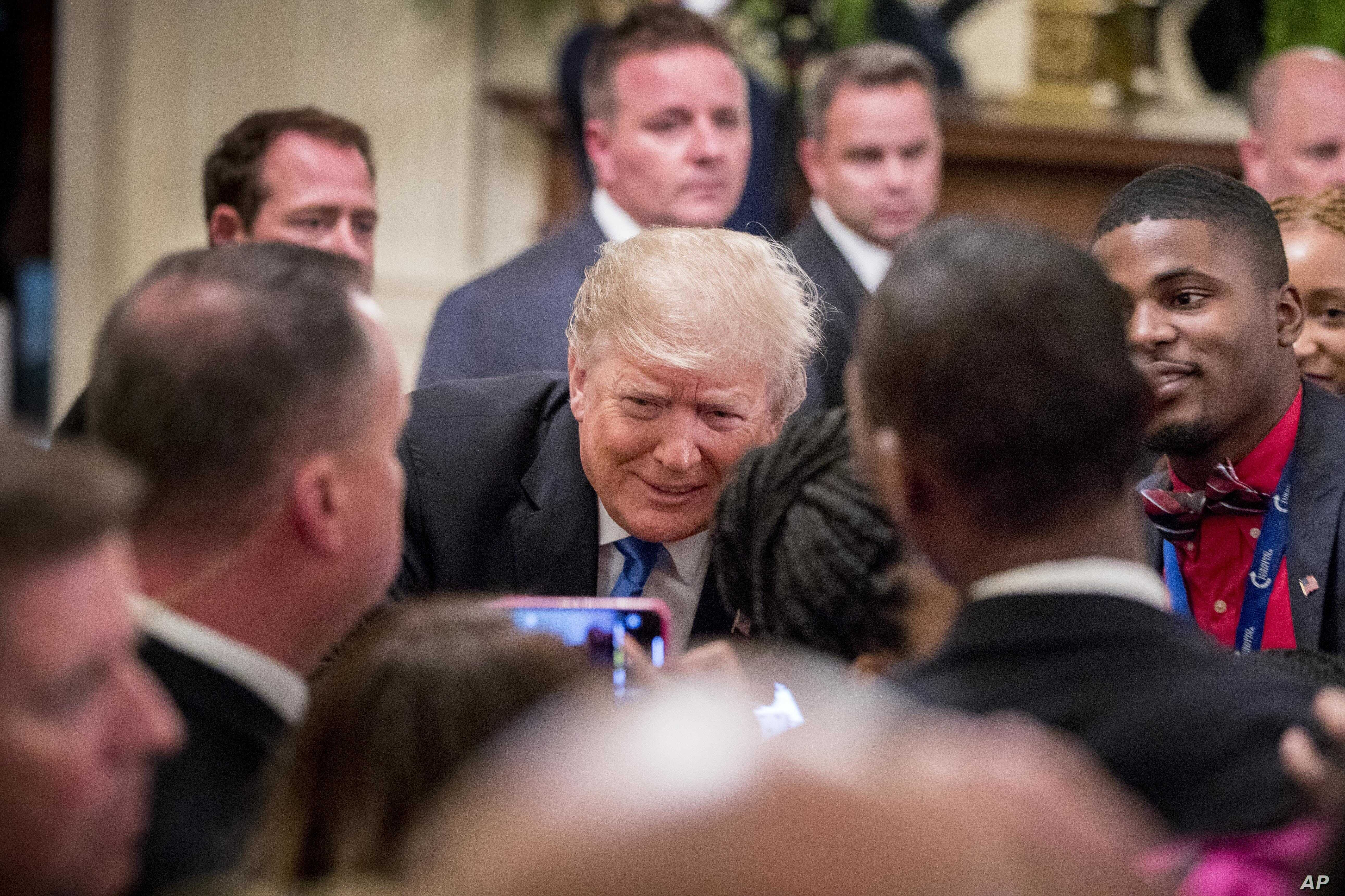 President Donald Trump takes a photograph with a member of the audience after speaking at the 2018 Young Black Leadership Summit in the East Room of the White House, Oct. 26, 2018, in Washington.