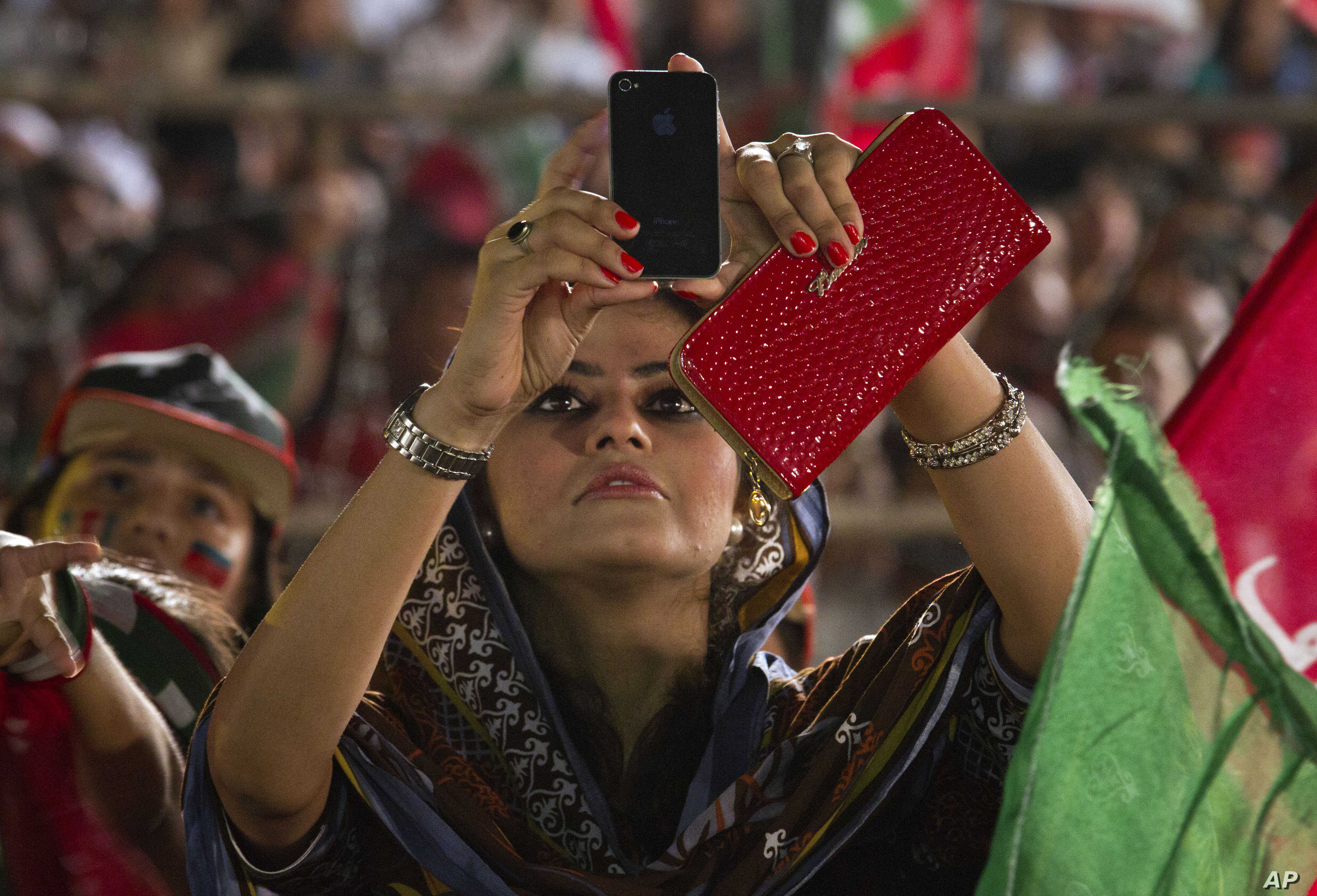 FILE - A woman uses her cell phone to take picture during a protest near the parliament building in Islamabad, Pakistan, Aug. 25, 2014.