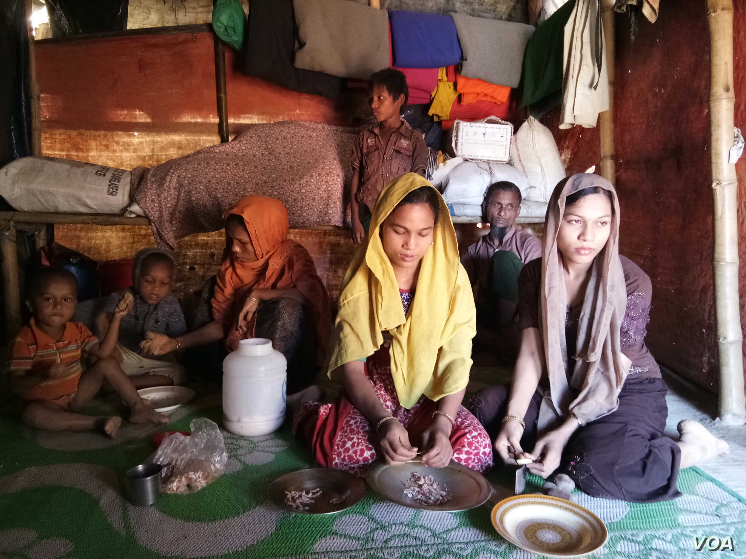 Noor Ankis, the mother of Rohingya sisters Johora (in yellow scarf), 12, and Jannatara, 14, finds it difficult to feed her family with the food rations she gets and plans to marry off her underage daughters as soon as possible. (Photos by Noor Hossai...