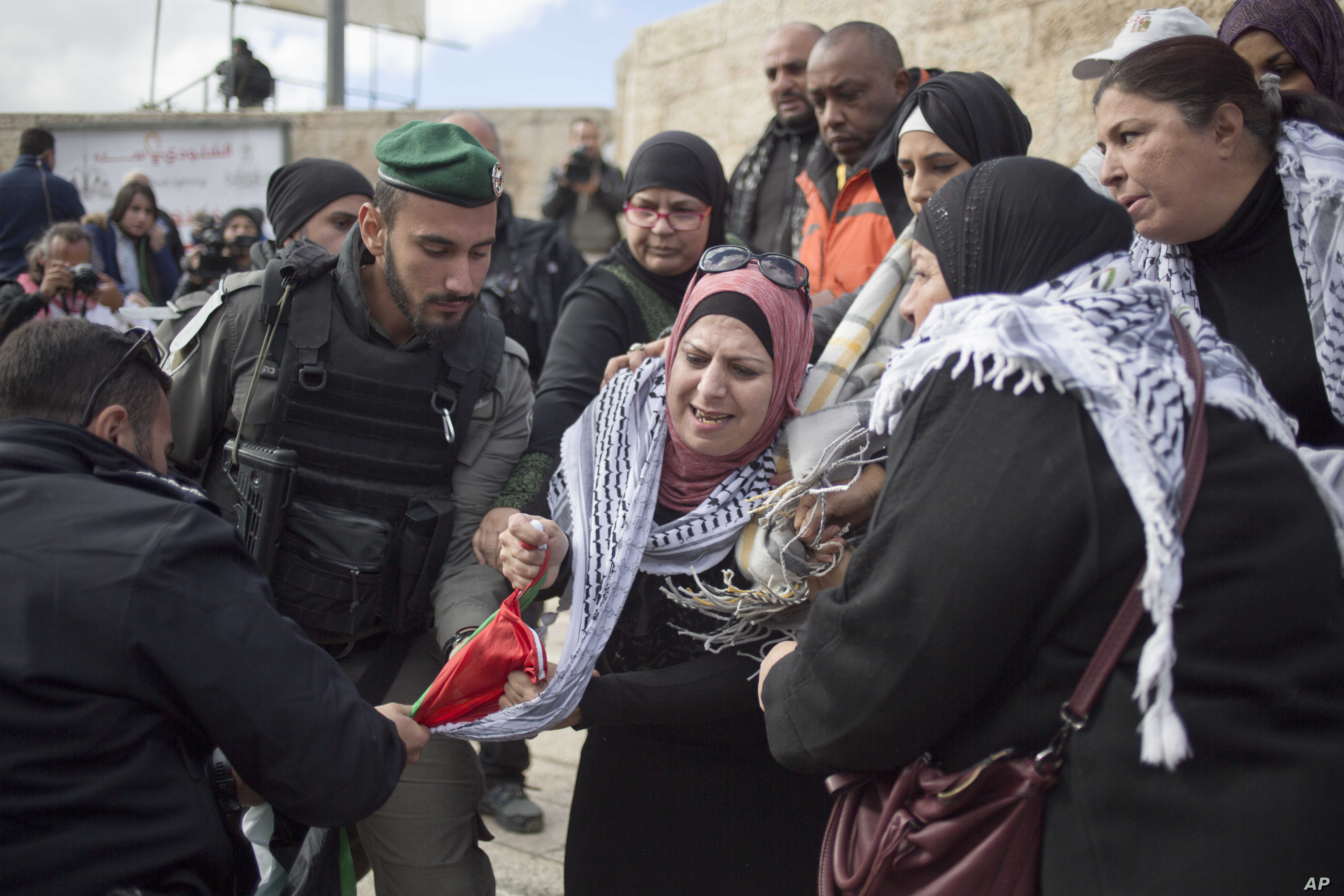 Israeli police officers try to remove a Palestinian flag from Palestinian women protesting outside the Damascus Gate in Jerusalem's Old City, Dec. 7, 2017.