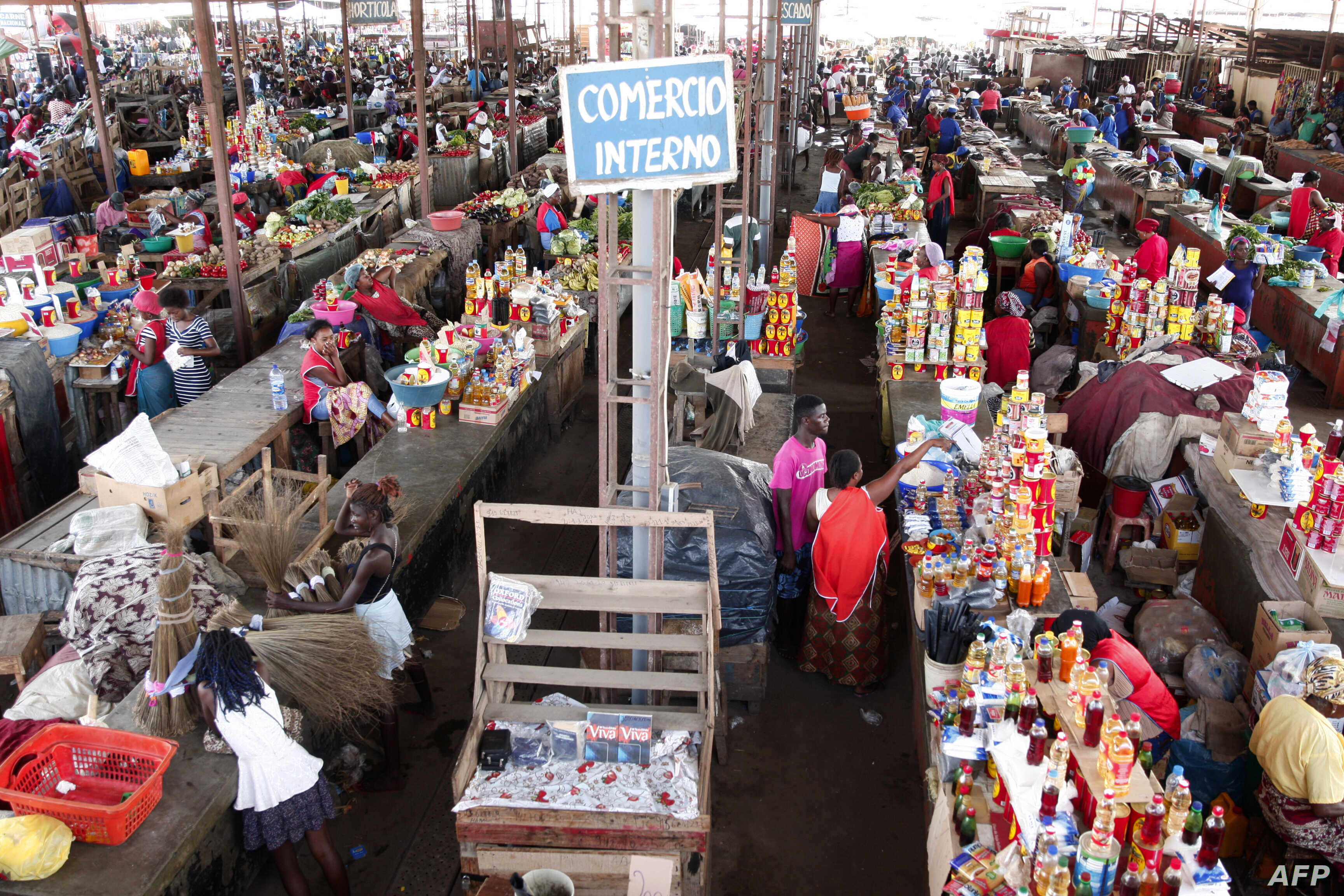 "People shop at a market in Luanda, Angola, Jan. 19, 2018. Angolan President Joao Lourenco was elected five months ago promising an ""economic miracle"". But the path to transforming the oil-dependent country's system will be long and difficult."