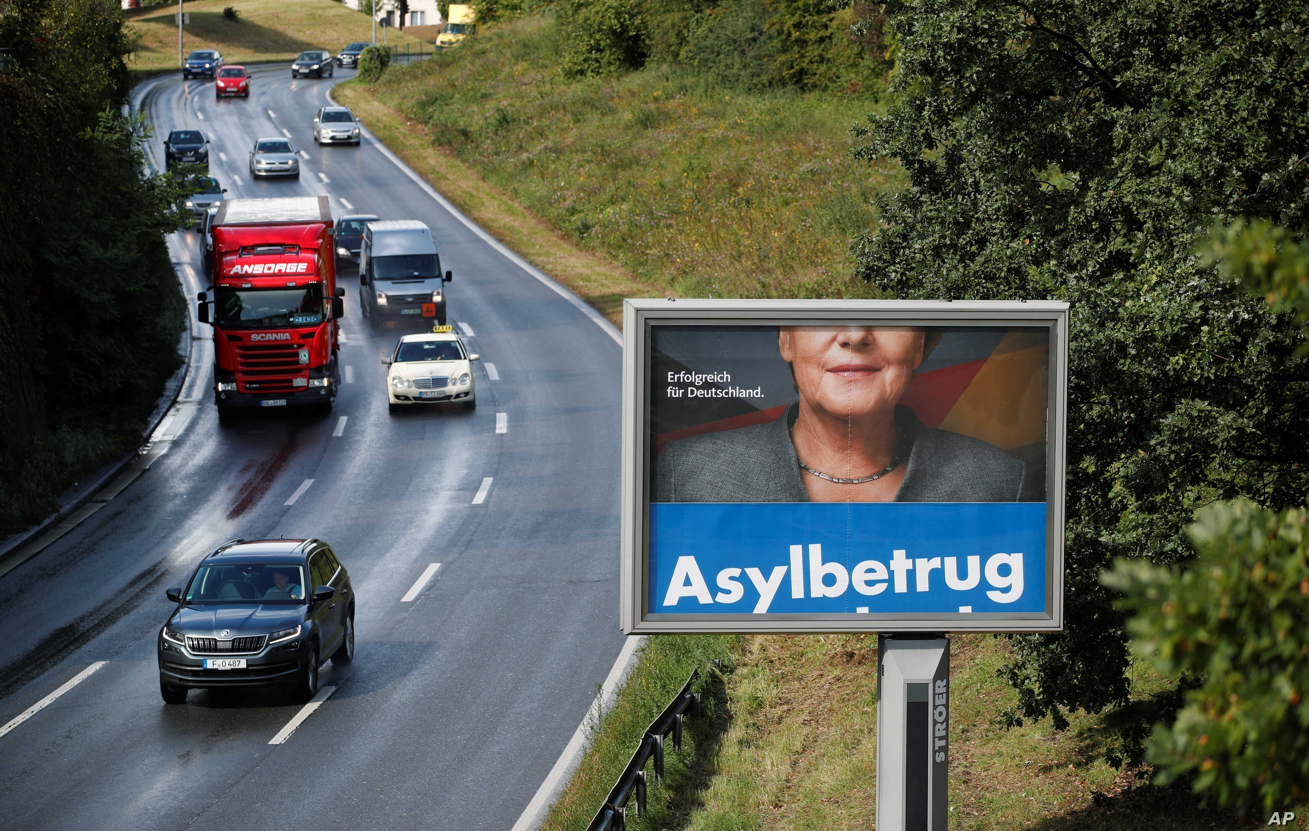 """FILE - A revolving election campaign poster of Germany's anti-immigration party, Alternative fuer Deutschland, AfD, reads """"Asylum fraud"""" as Angela Merkel, German chancellor and leader of the Christian Democratic Union party, CDU, appears partly on a ..."""