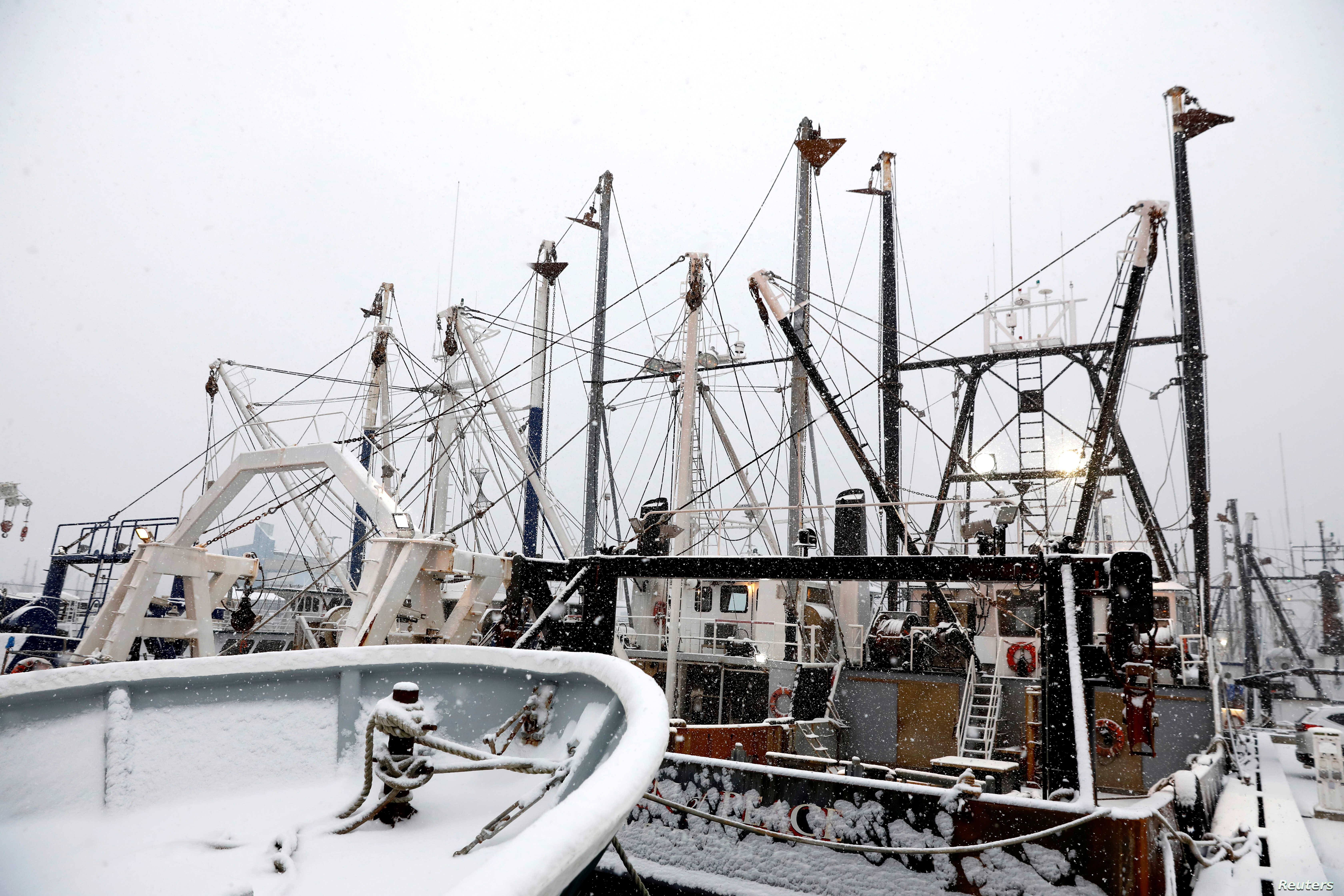 Snow-covered fishing boats are seen in New Bedford, Massachusetts, Dec. 14, 2017.