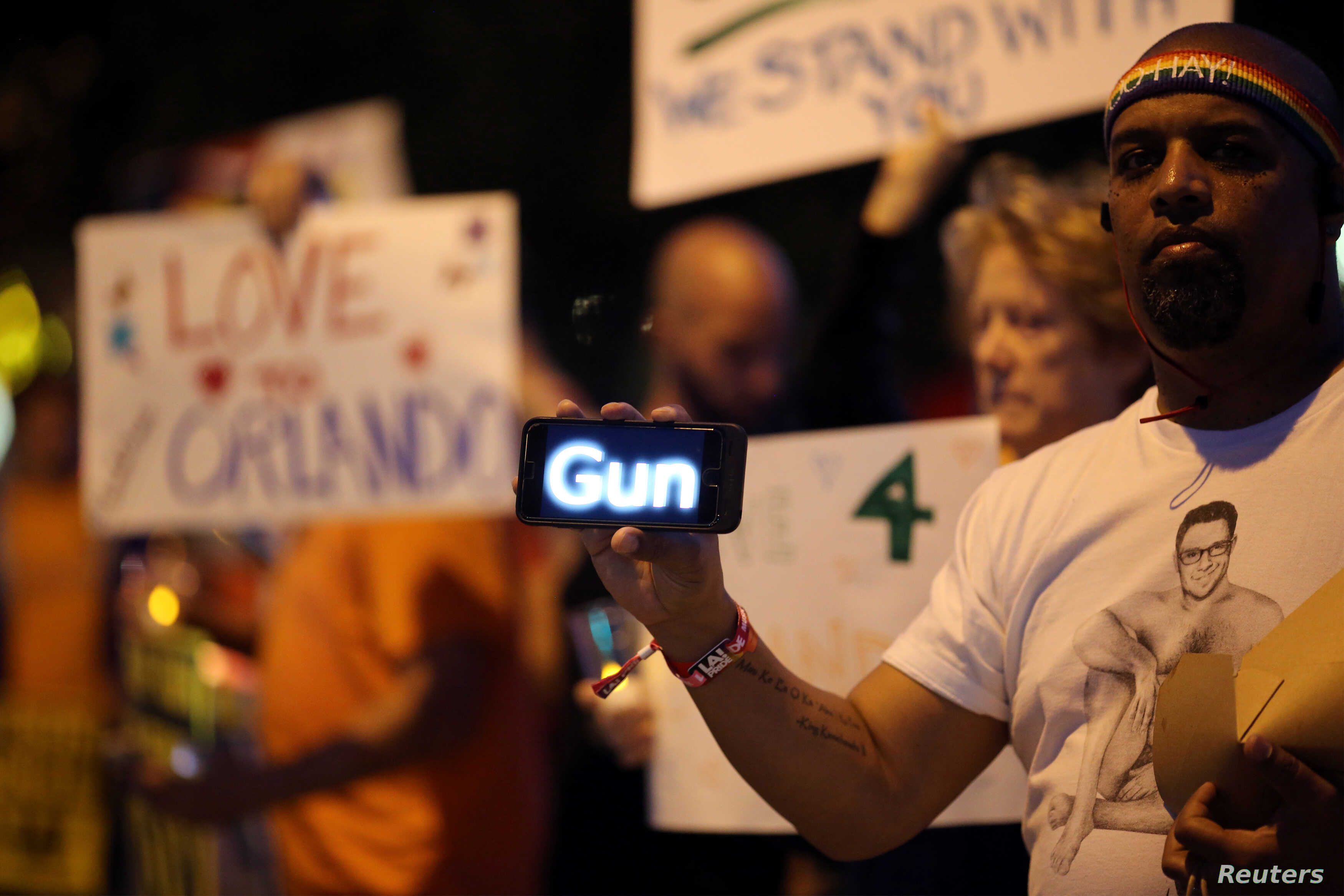 A man holds a scrolling message about guns on his smart phone at a candlelight vigil in West Hollywood, California, following the early morning attacks on a gay night club in Orlando, Florida, U.S. June 12, 2016.