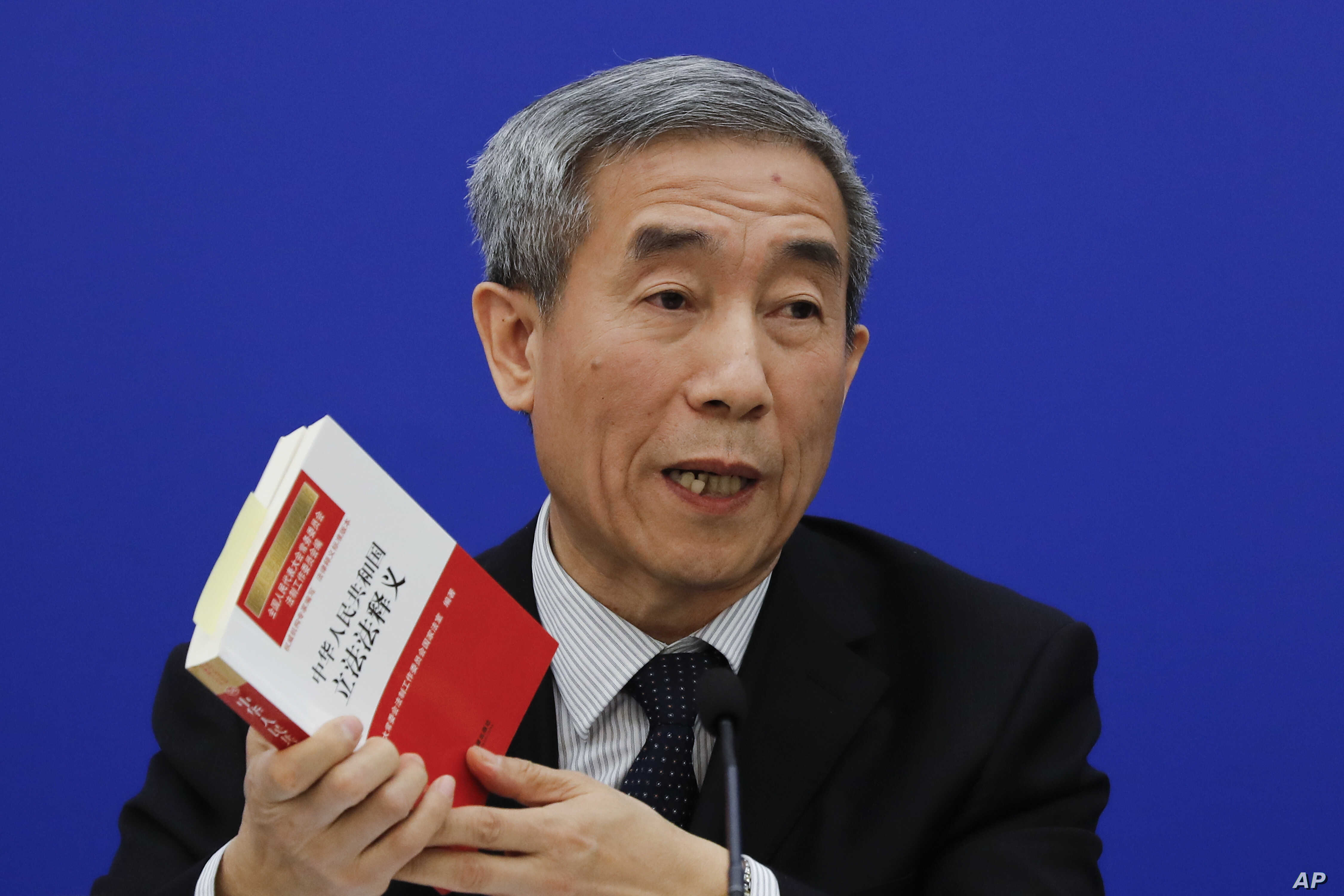 Li Fei, deputy secretary general of the National People's Congress Standing Committee, holds a China's legislation law book while speaking during a press conference at the Great Hall of the People in Beijing, Nov. 7, 2016.