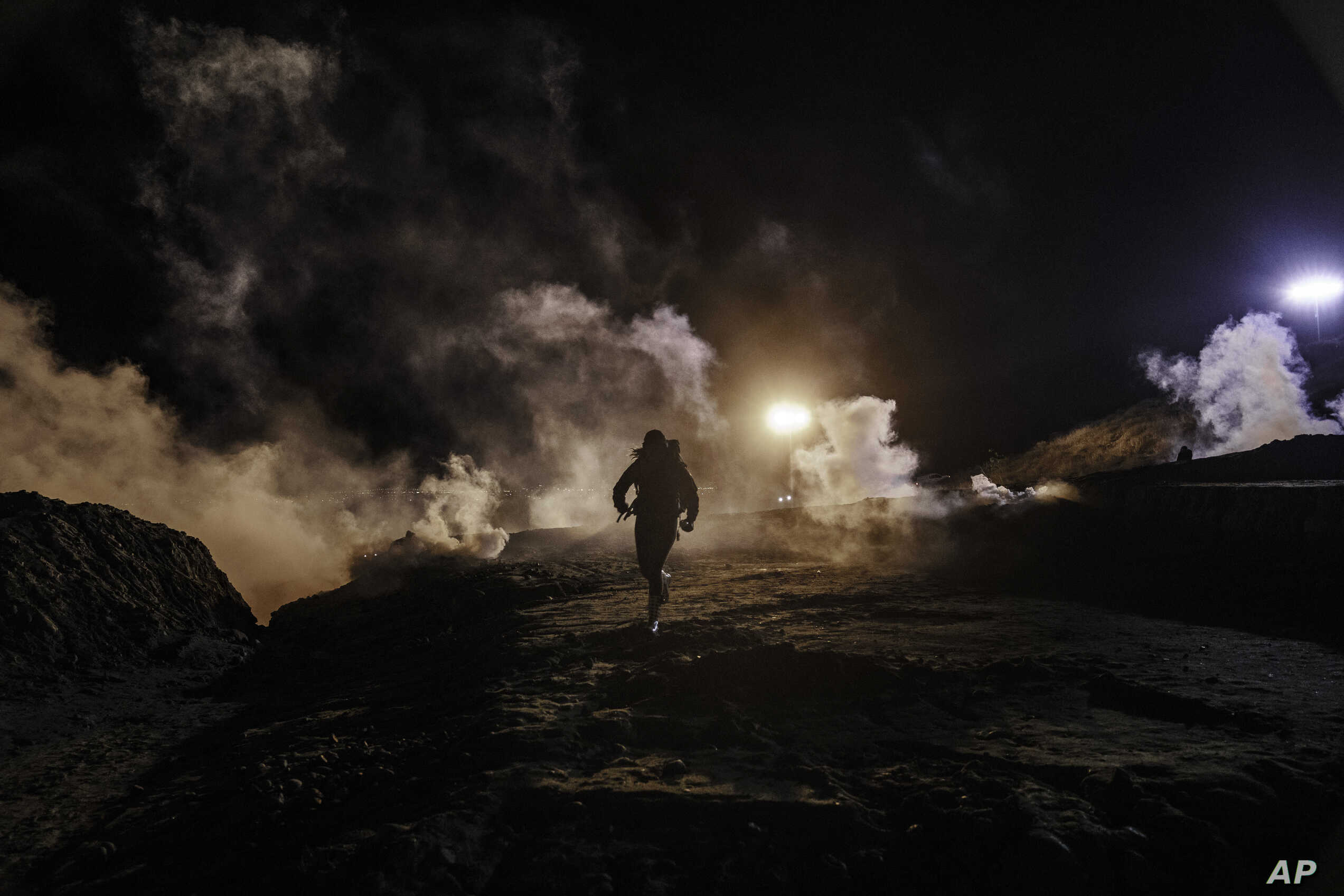 Migrants run as tear gas is thrown by U.S. Border Protection officers to the Mexican side of the border fence after they climbed the fence to get to San Diego, from Tijuana, Mexico, Jan. 1, 2019.