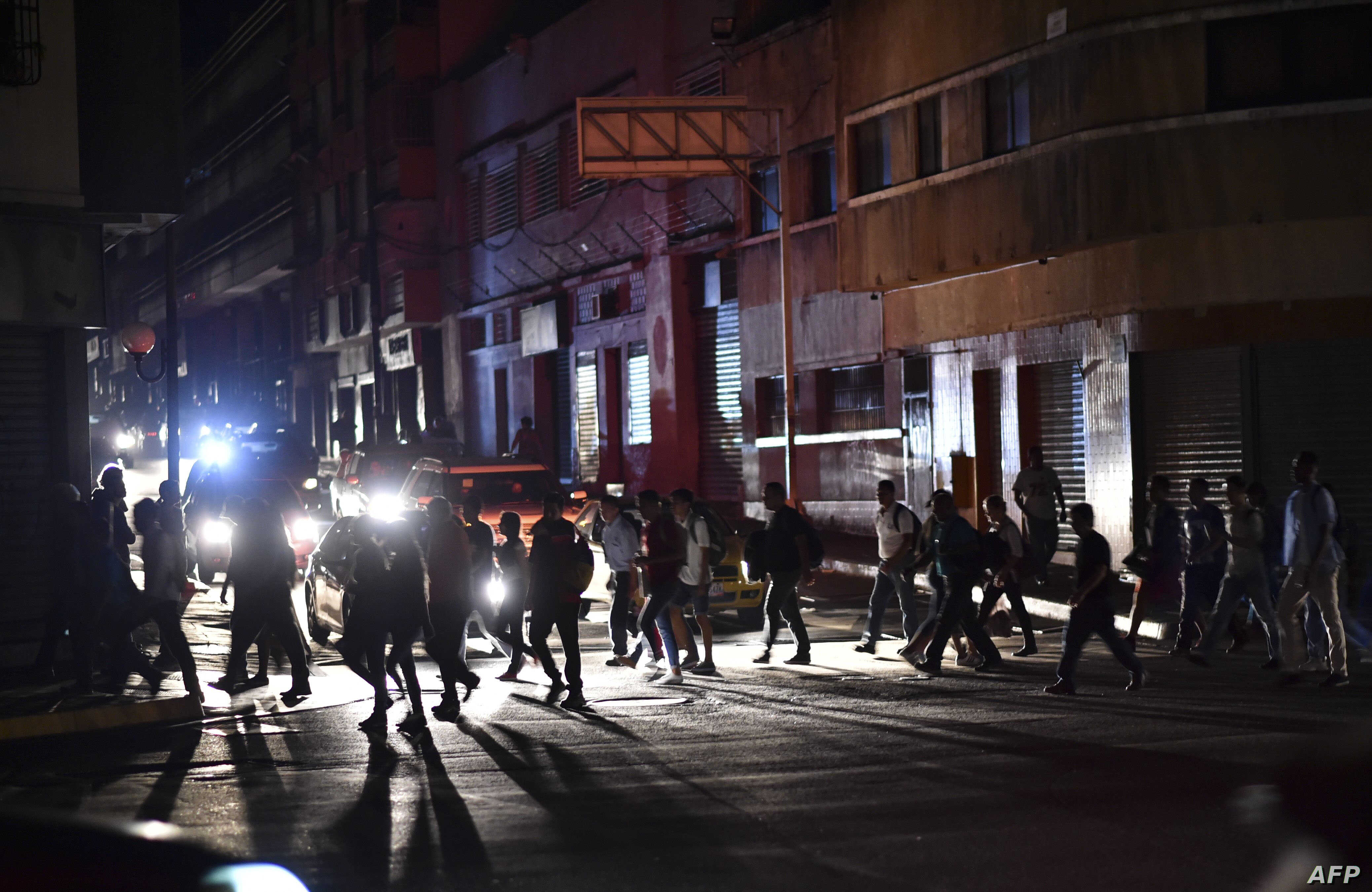 People cross a street during a power cut in Caracas on March 7, 2019.