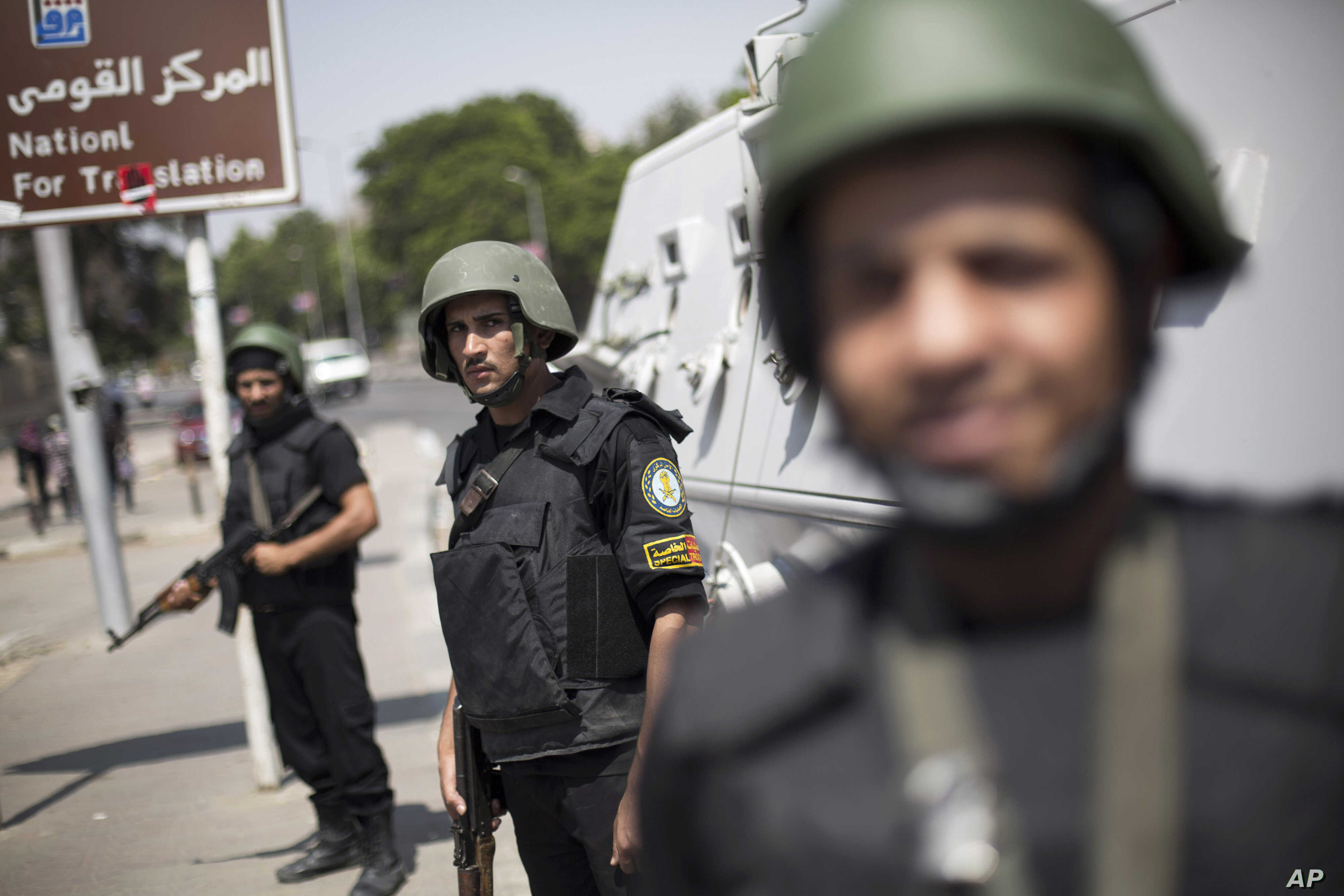 Egyptian police special forces stand guard beside an armored vehicle, protecting a bridge between Tahrir Square and Cairo University, where Muslim Brotherhood supporters have gathered, in Giza, Egypt, July 3, 2013.