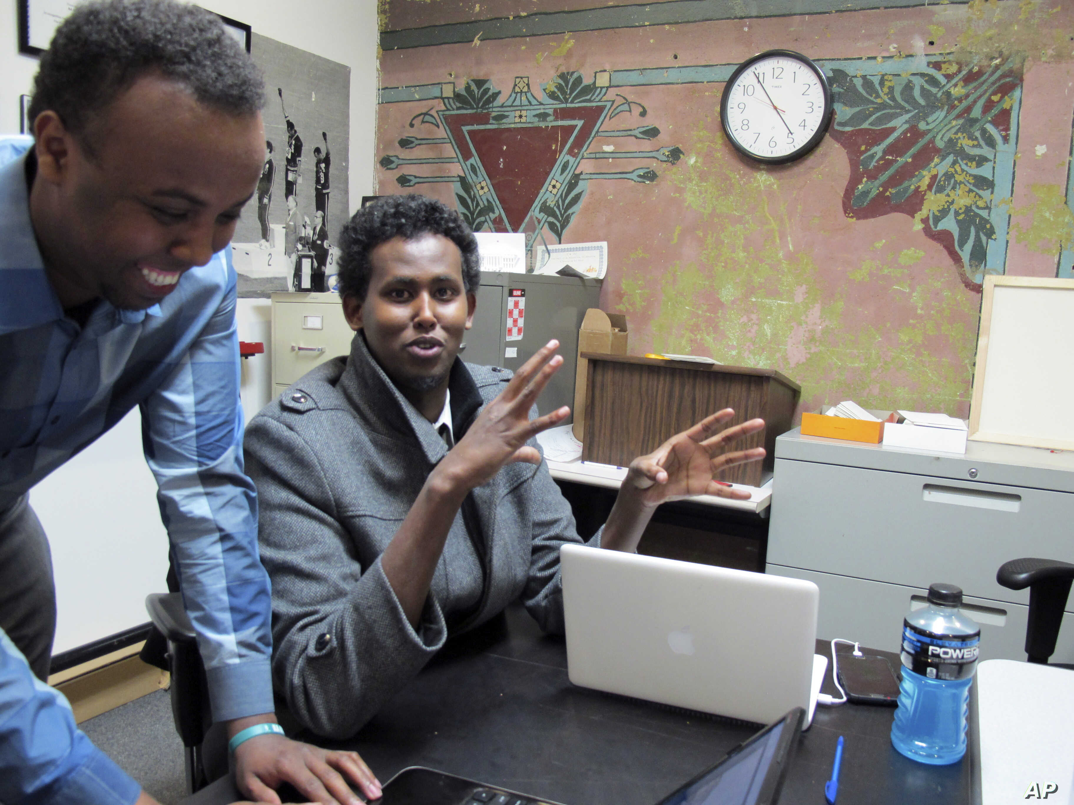 FILE - Mohamed Farah (left) executive director of Ka Joog, talks with Vice President Daud Mohamed in Minneapolis, Feb. 27, 2014. Ka Joog is a Somali nonprofit organization in Minneapolis that has turned down money from the Trump Administration.