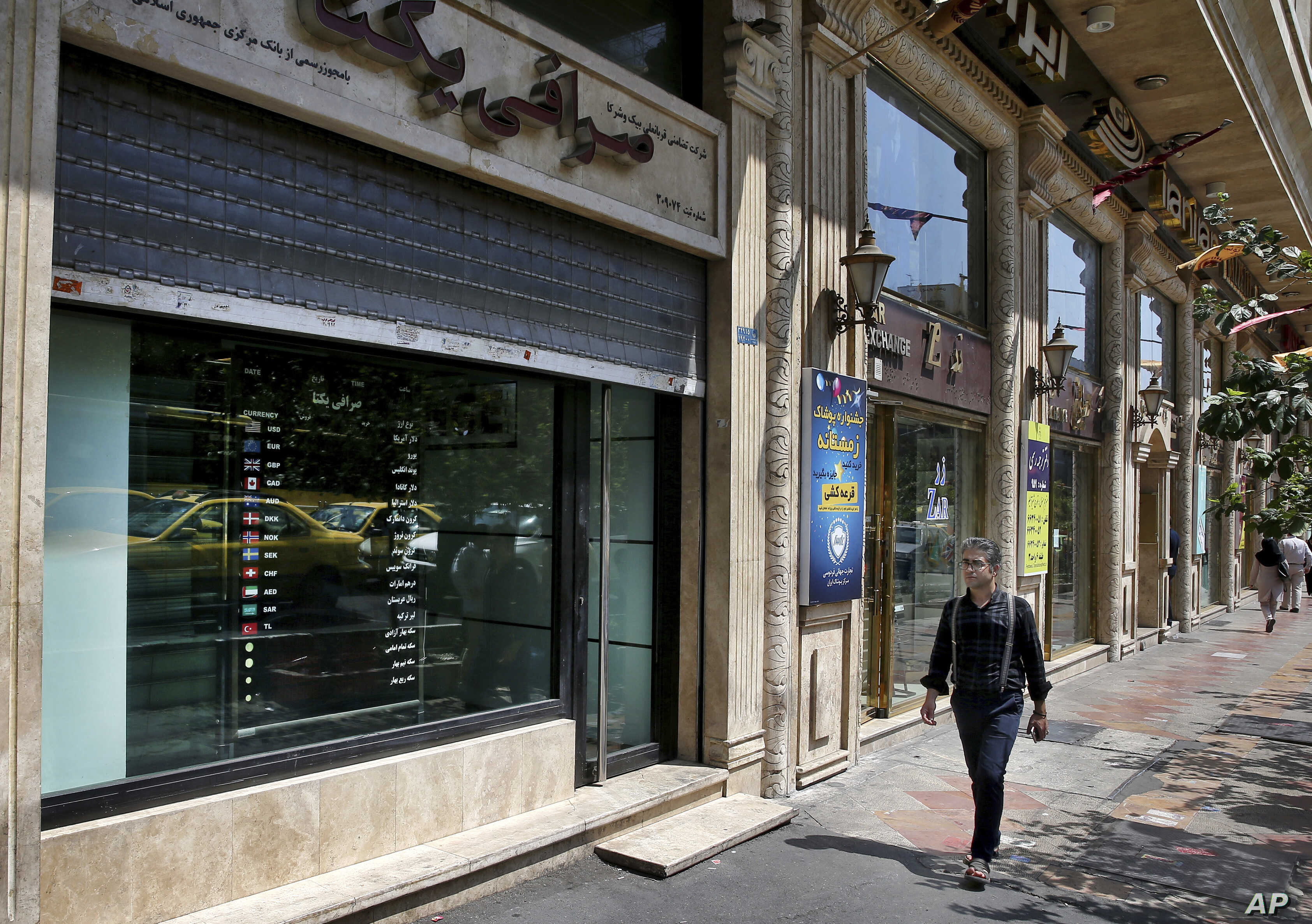 Currency exchange shops line a street in downtown Tehran, Iran, Aug. 7, 2018. Money exchange shops across Iran cautiously reopened on Tuesday after being shut for five months.