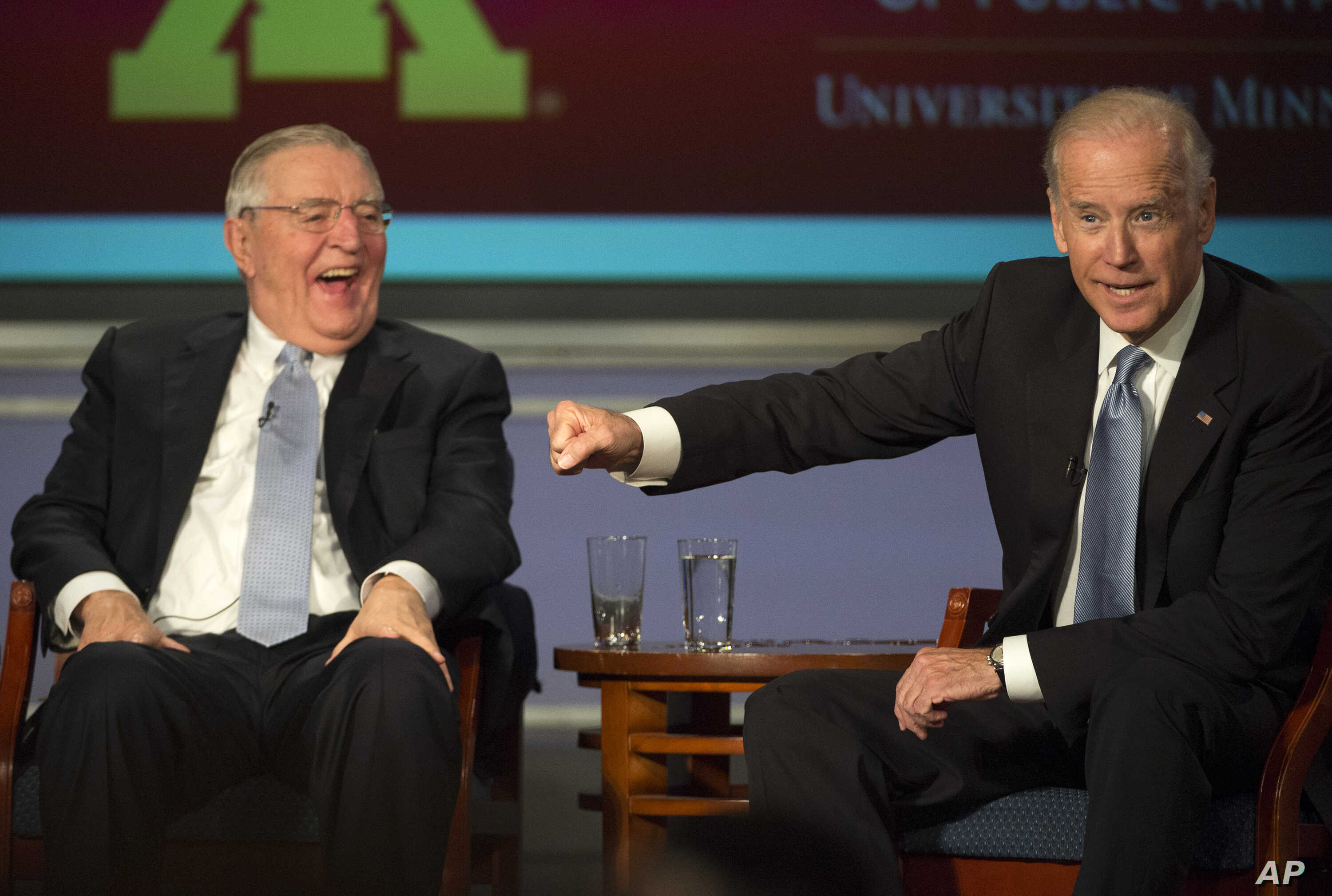 Vice President Joe Biden gestures toward former Vice President Walter Mondale as they participate in a forum honoring Mondale's legacy, at George Washington University in Washington, Oct. 20, 2015.