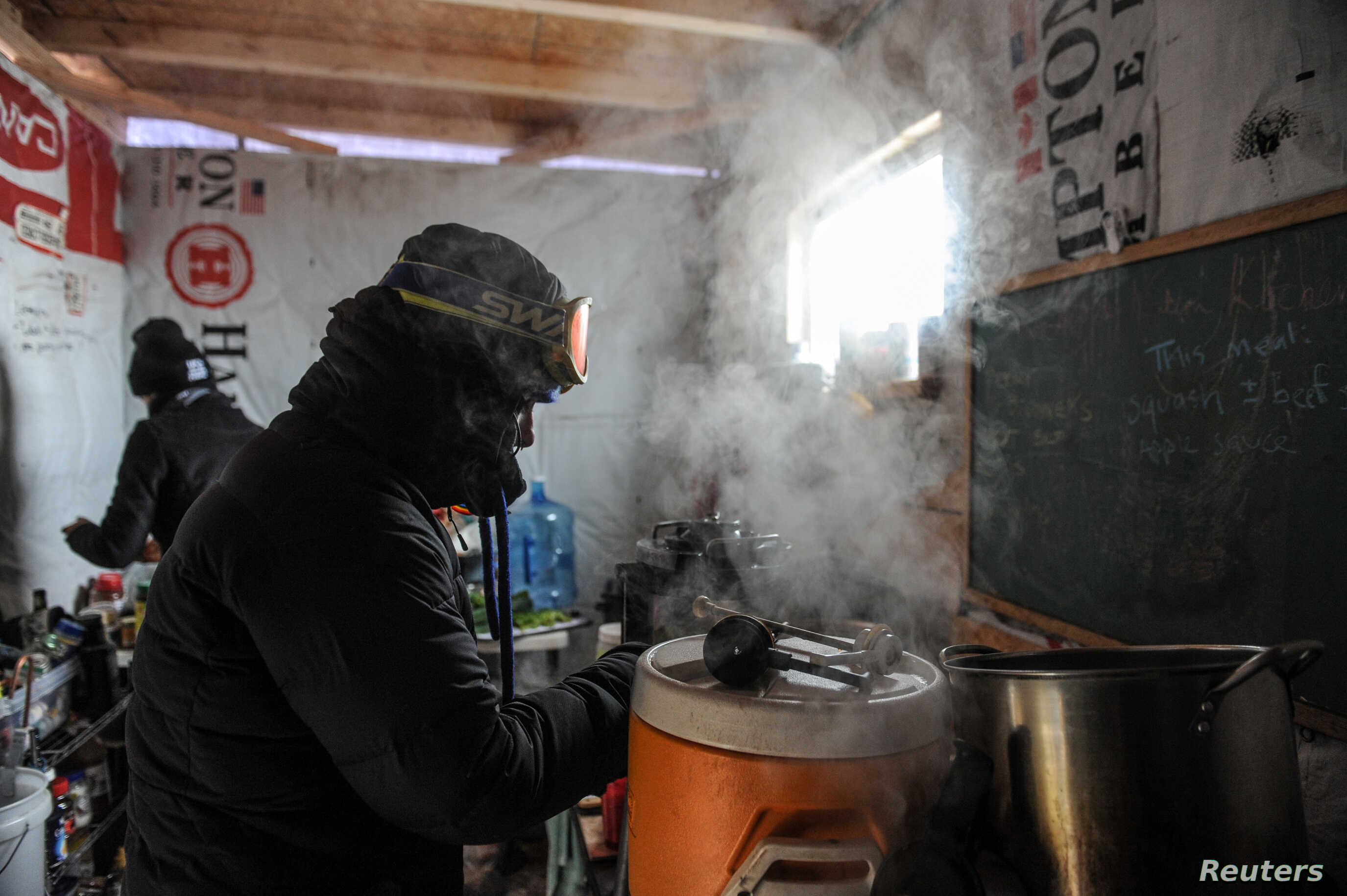 "A woman makes coffee in a kitchen in the Oceti Sakowin camp as ""water protectors"" continue to demonstrate against plans to pass the Dakota Access pipeline near the Standing Rock Sioux Reservation, near Cannon Ball, N.D., Dec. 6, 2016."