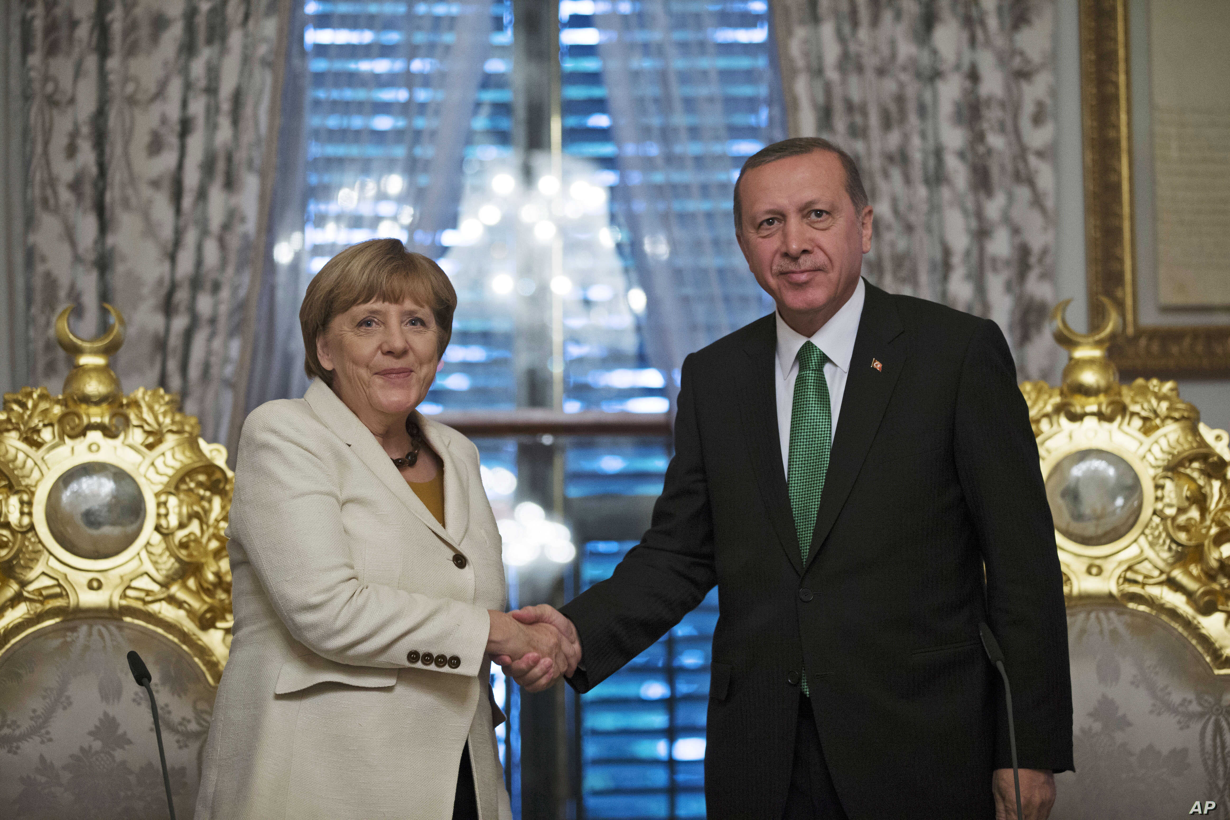 Turkish President Recep Tayyip Erdogan, right, shakes hands Germany's Chancellor Angela Merkel, left, following a joint statement after their meeting in Istanbul, Oct. 18, 2015.