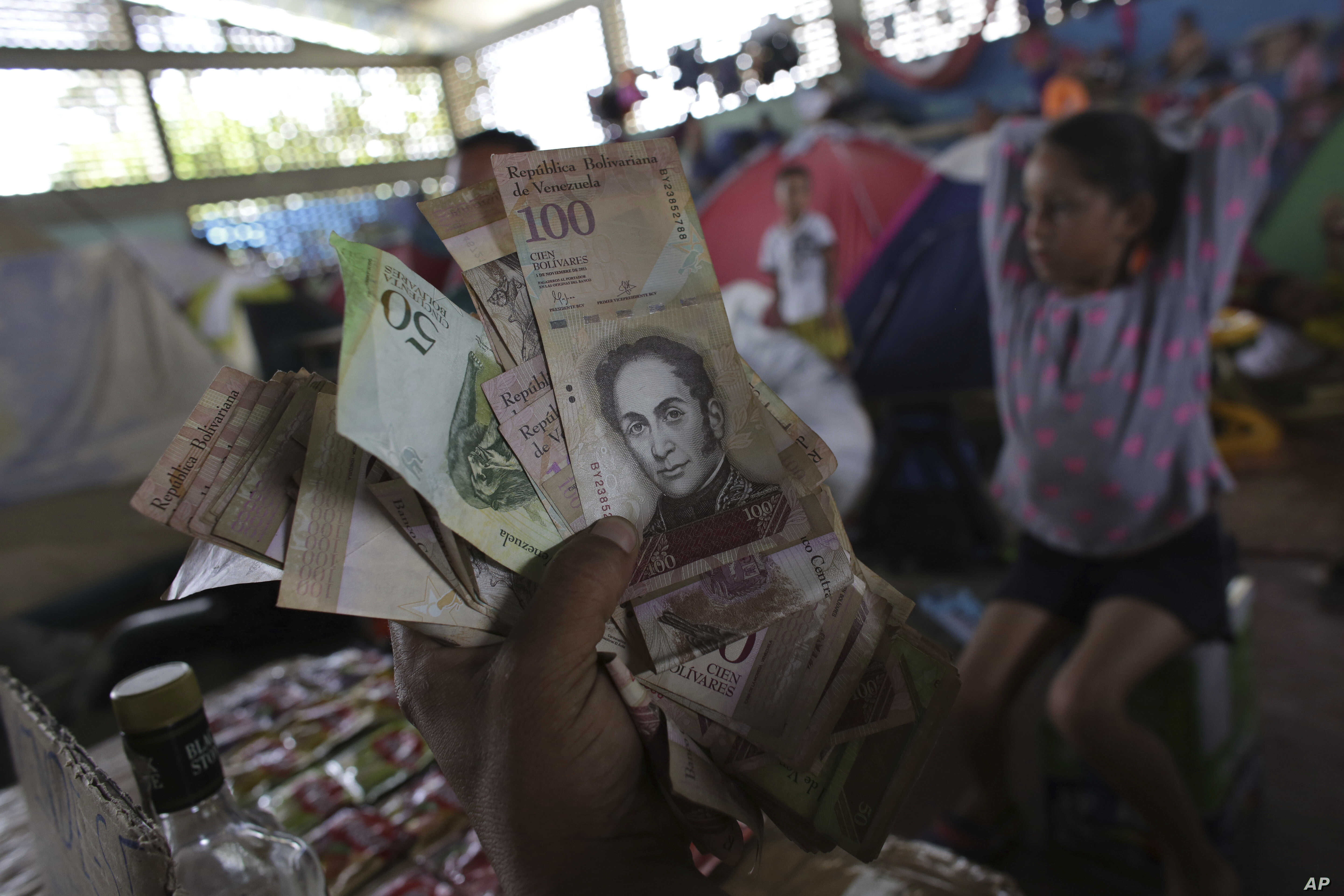 In this March 8, 2018 photo, Venezuelan Charlie Ivan Delgado shows his country's currency as he talks about the economic crisis at a migrant shelter that offers three meals a day where he brought his family of five in Boa Vista, Brazil.