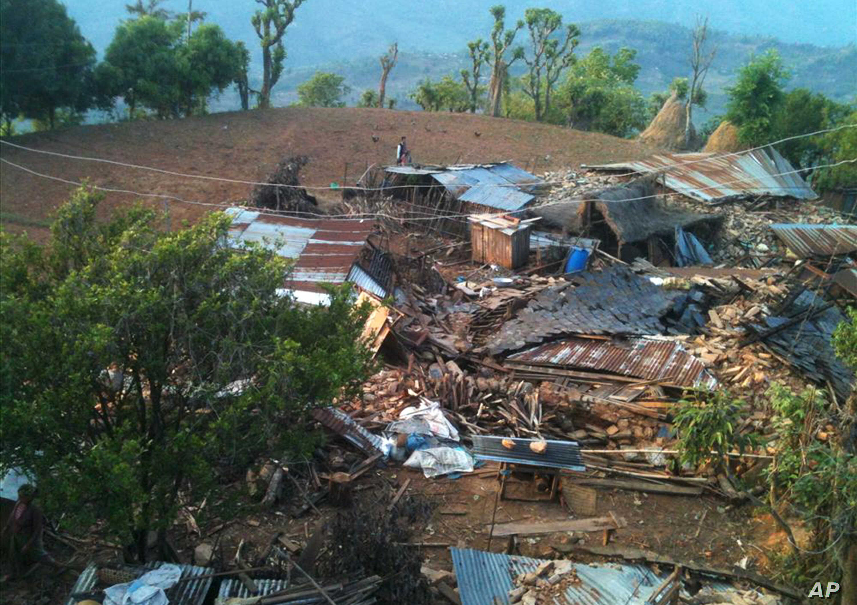In this photo provided by World Vision, houses lie destroyed by Saturday's earthquake at Paslang village in Gorkha municipality, Nepal, April 27, 2015.