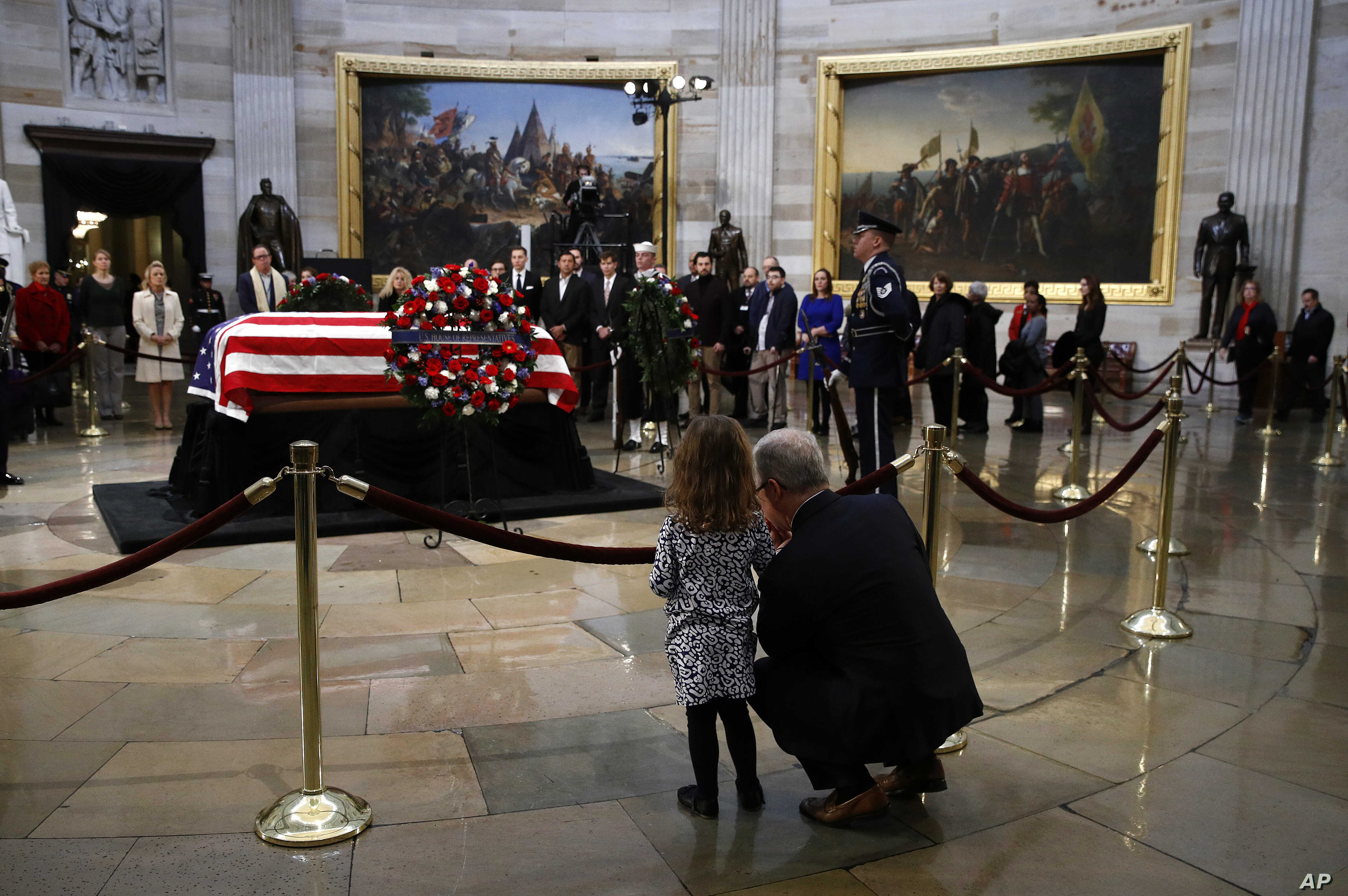 Rep. Patrick McHenry, R-N.C., kneels alongside his daughter Cecelia near the flag-draped casket of former President George H.W. Bush as he lies in state in the Capitol Rotunda in Washington, Dec. 4, 2018.