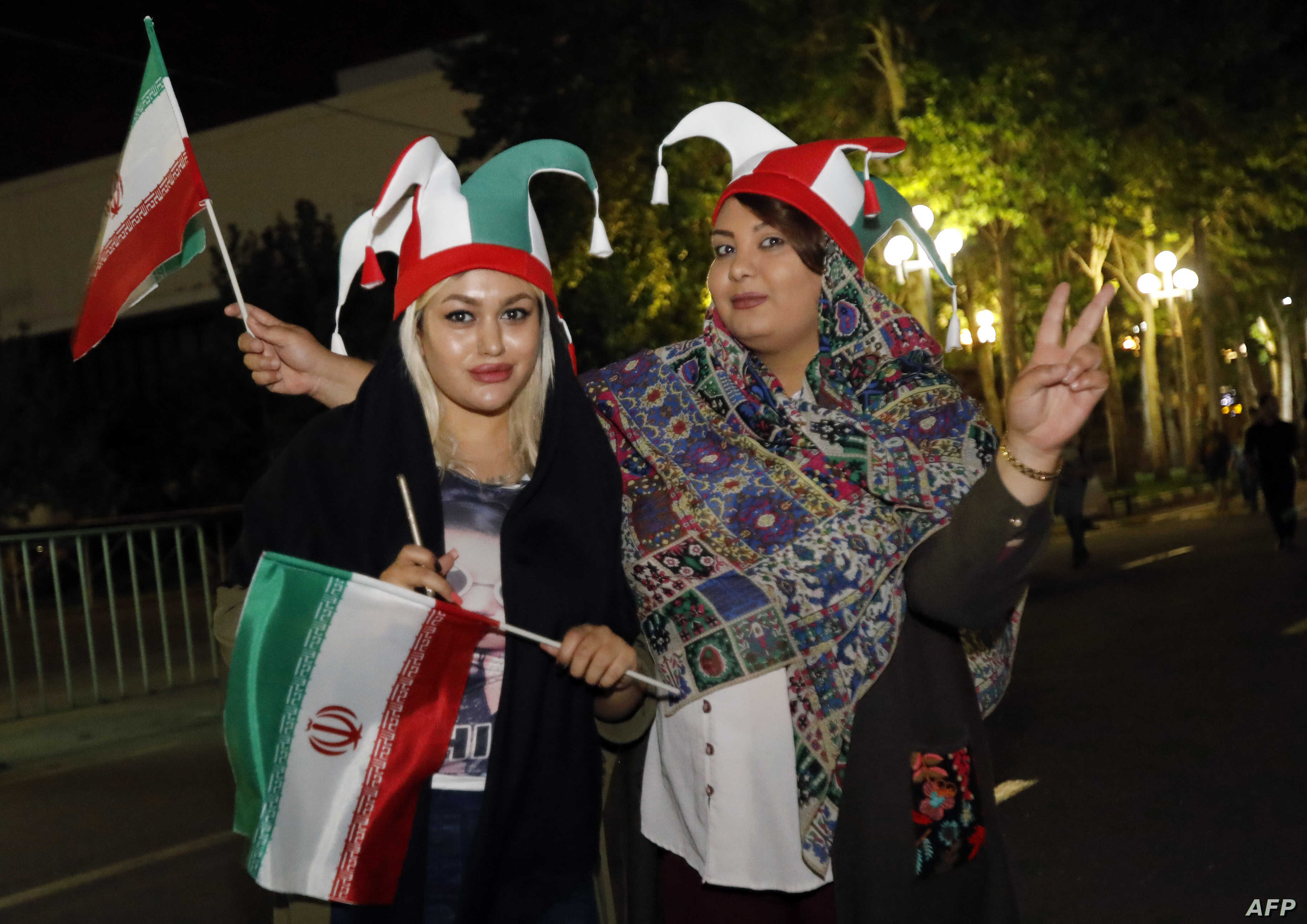 Iranian football supporters wearing the national football team's colors wave national flags outside Azadi stadium in Tehran, June 20, 2018, during a screening of the Russia 2018 World Cup Group B football match between Iran and Spain. Tehran's larges...