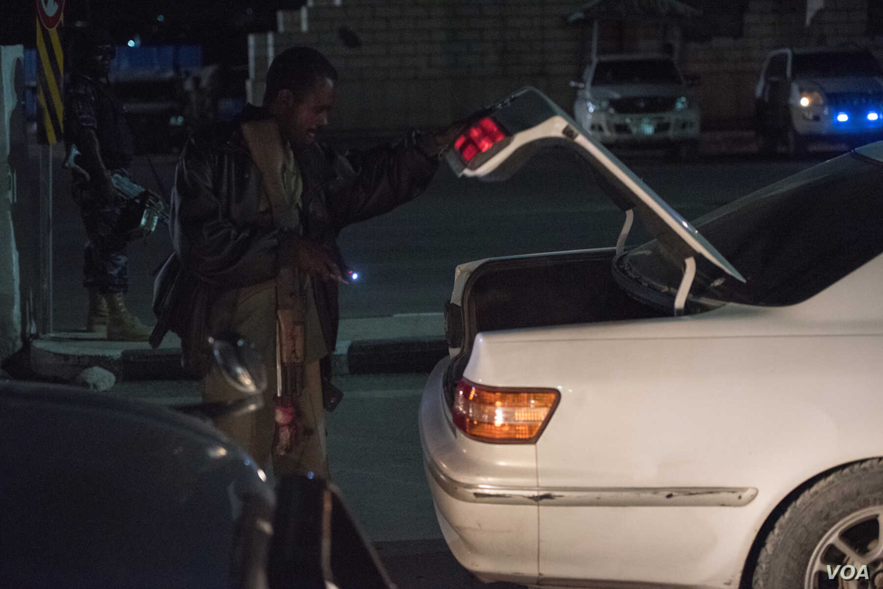 A Somali security officer checks the trunk of a car at a checkpoint in Mogadishu, Sept. 20, 2016. (Photo: J. Patinkin/VOA)