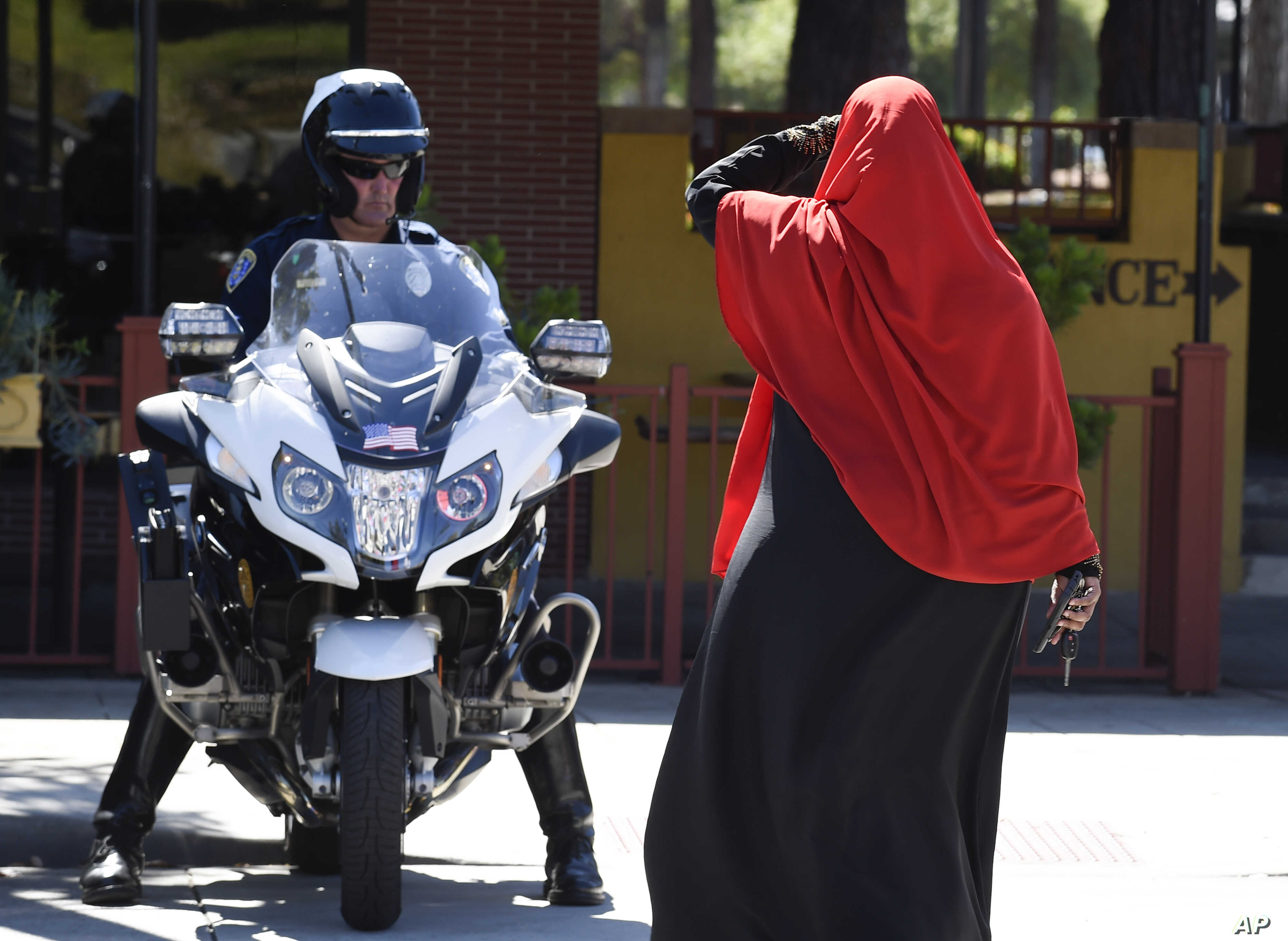 FILE - A Muslim woman leaves a protest as a San Diego police officer looks on after protesters marched through El Cajon, Calif., Oct. 1, 2016, in reaction to the fatal police shooting of an unarmed black man, Alfred Olango  Olango.