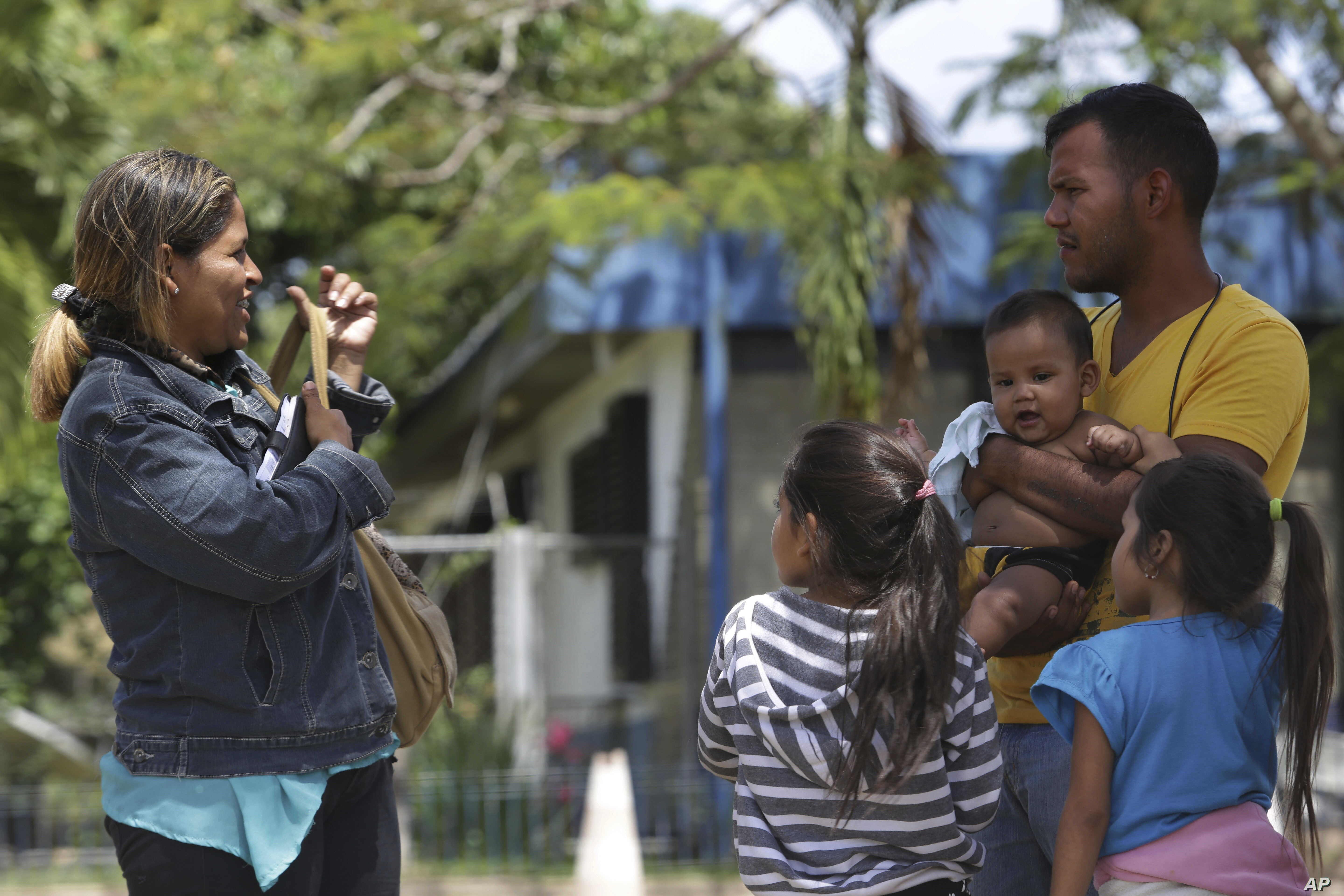 In this March 9, 2018 photo, Venezuelan Kritce Montero and her husband Hector Espinosa stand with their children, 6-month-old Hector, their 7-year-old daughter, right, and an unidentified family member, after getting their documents to enter Brazil.