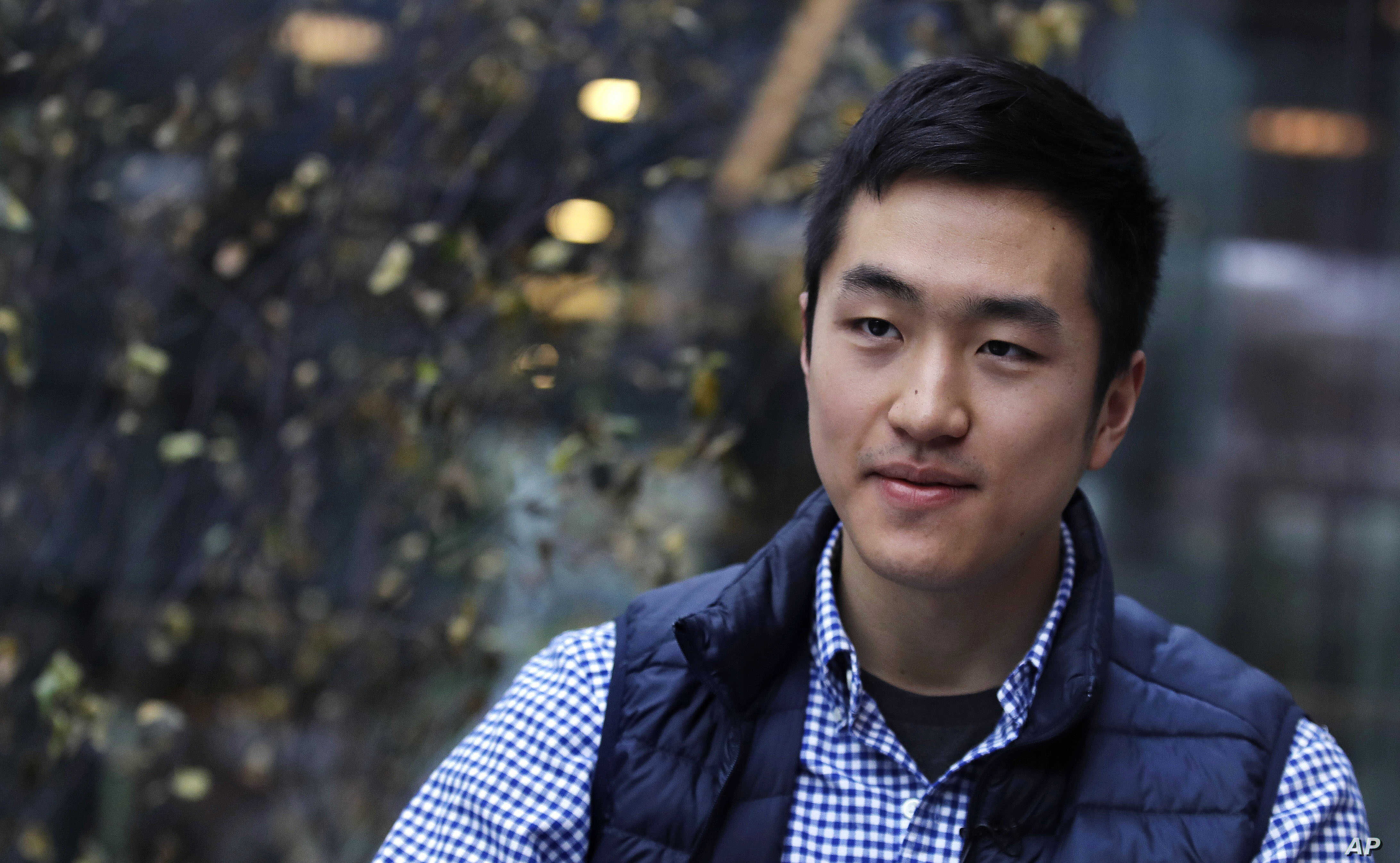 Harvard University graduate Jin K. Park, who holds a degree in molecular and cellular biology, listens during an interview in Cambridge, Mass., Thursday, Dec. 13, 2018. (AP Photo/Charles Krupa)