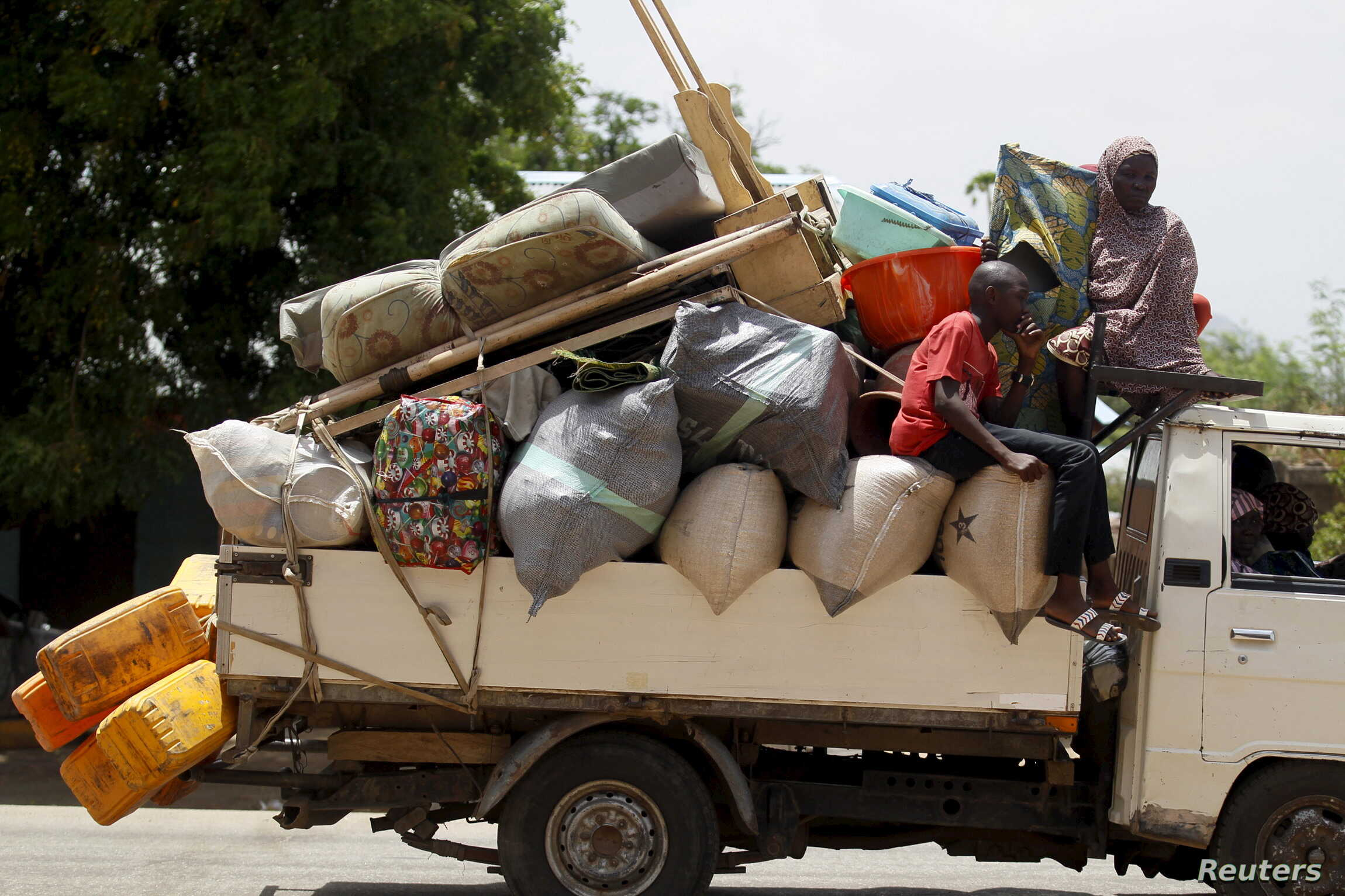 People travel in a truck with their belongings as they return after the Nigerian military recaptures the town of Michika from Boko Haram, Adamawa state, May 10, 2015.