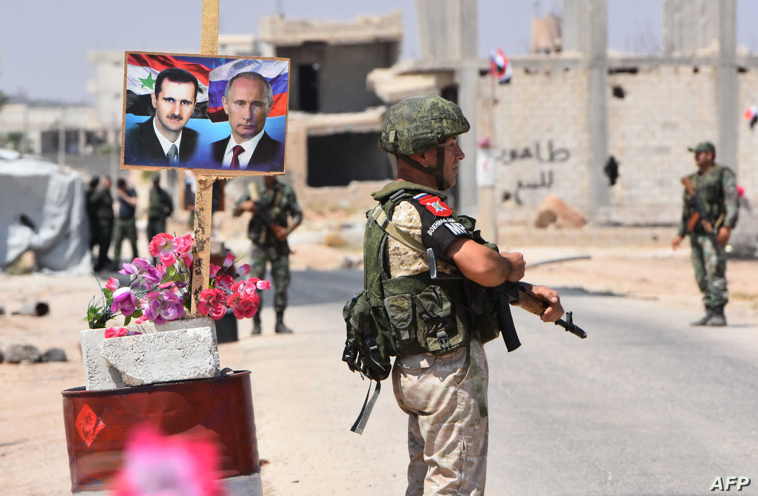 Members of Russian and Syrian forces stand guard near posters of Syrian President Bashar al-Assad and his Russian counterpart Vladimir Putin at the Abu Duhur crossing on the eastern edge of Idlib province, Aug. 20, 2018.