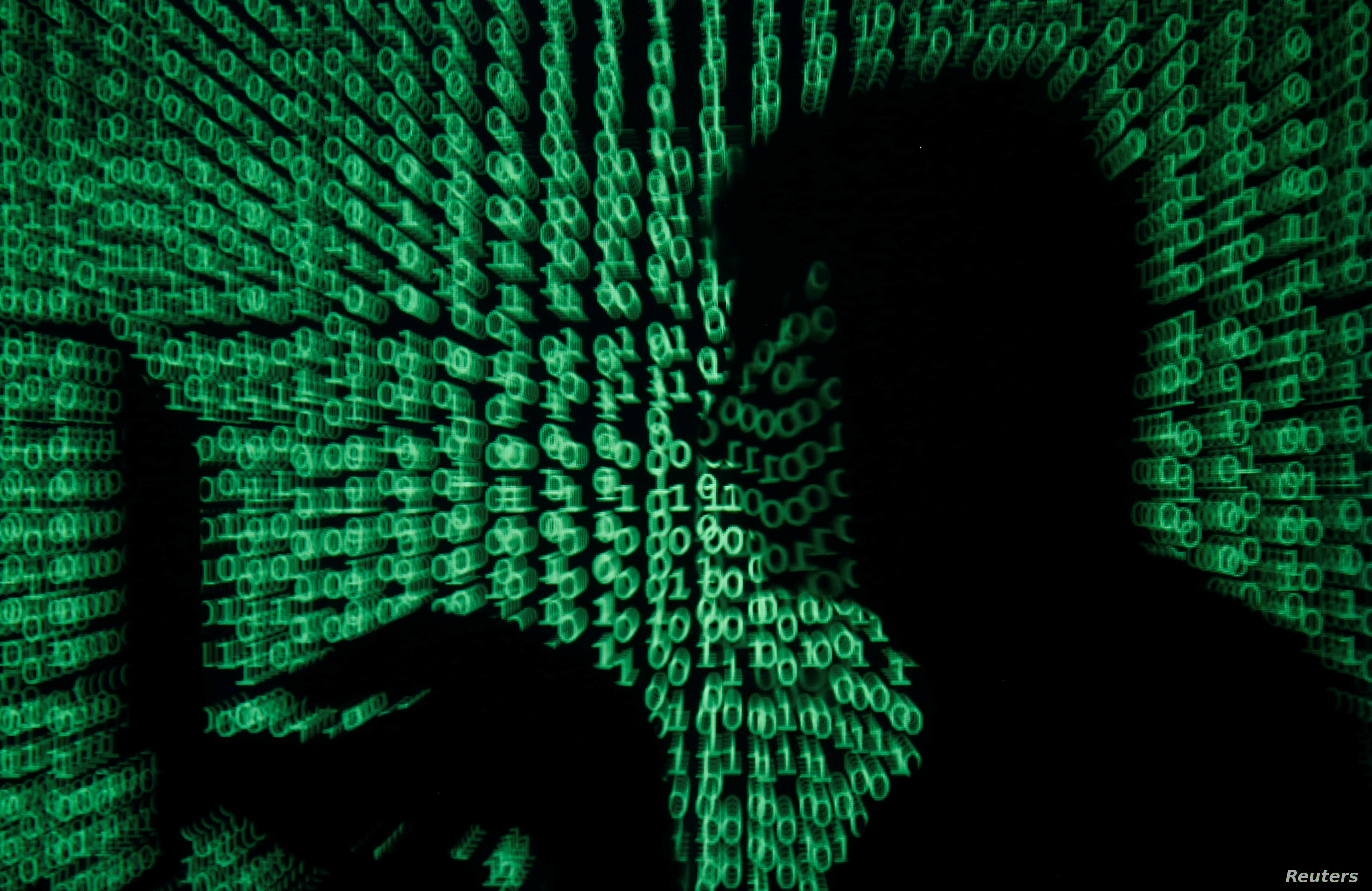 A man holds a laptop computer as code is projected on him in this illustration made on May 13, 2017. Capitalizing on spying tools believed to have been developed by the U.S. National Security Agency, hackers staged a cyberassault with a self-spreadin
