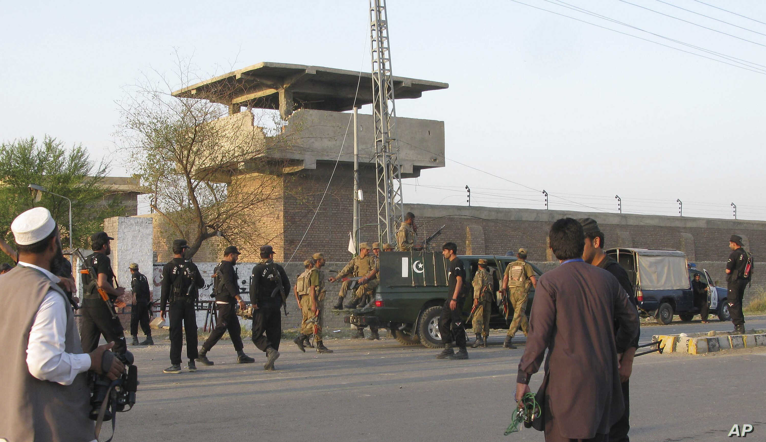 FILE - Pakistan army soldiers and other security officials surround a central jail in Bannu, 170 kilometers south of Peshawar, Pakistan. Taliban militants battled their way into this prison in 2012, freeing close to 400 prisoners.