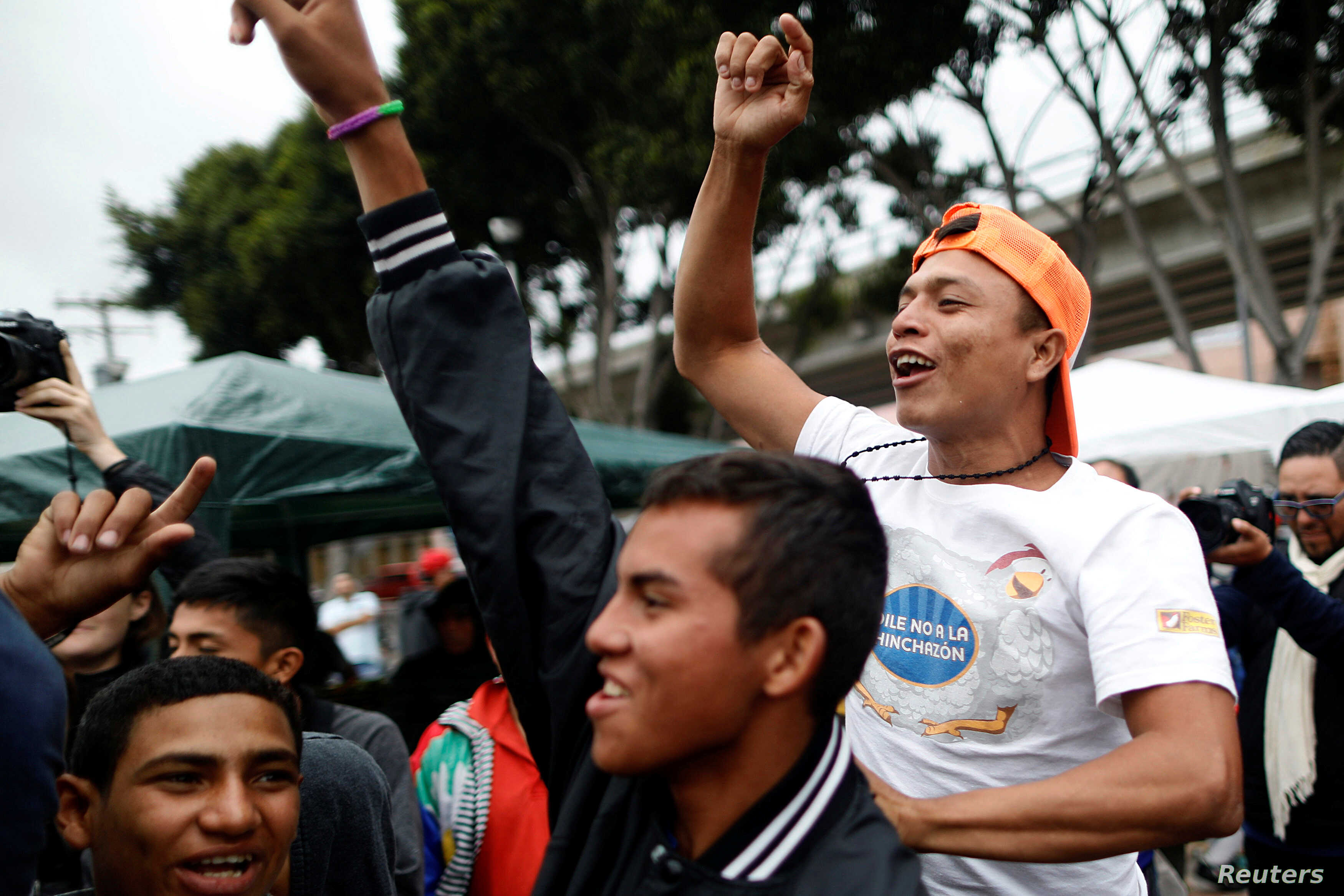 Members of a caravan of migrants from Central America react near the San Ysidro checkpoint as the first fellow migrants entered U.S. territory to seek asylum on Monday, in Tijuana, Mexico, April 30, 2018.
