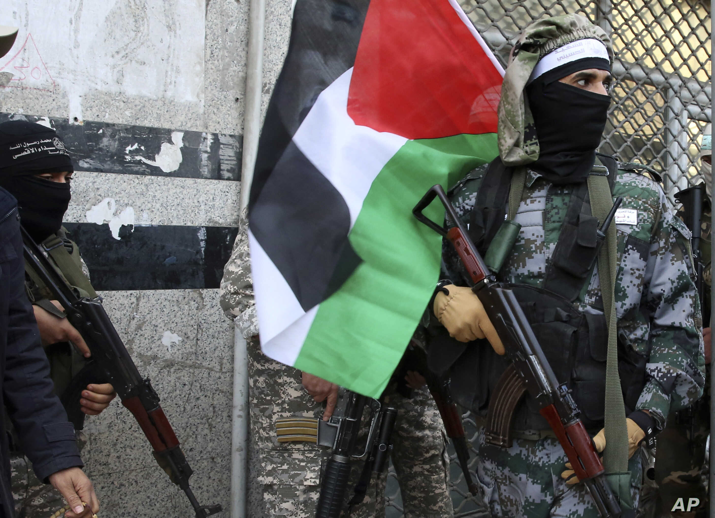 Masked militants from Al Aqsa Martyrs' Brigade, a militia linked to the Fatah movement, hold their rifles and the Palestinian flag during a protest to condemn the decision by President Trump to recognize Jerusalem as Israel's capital, in Gaza City, D...