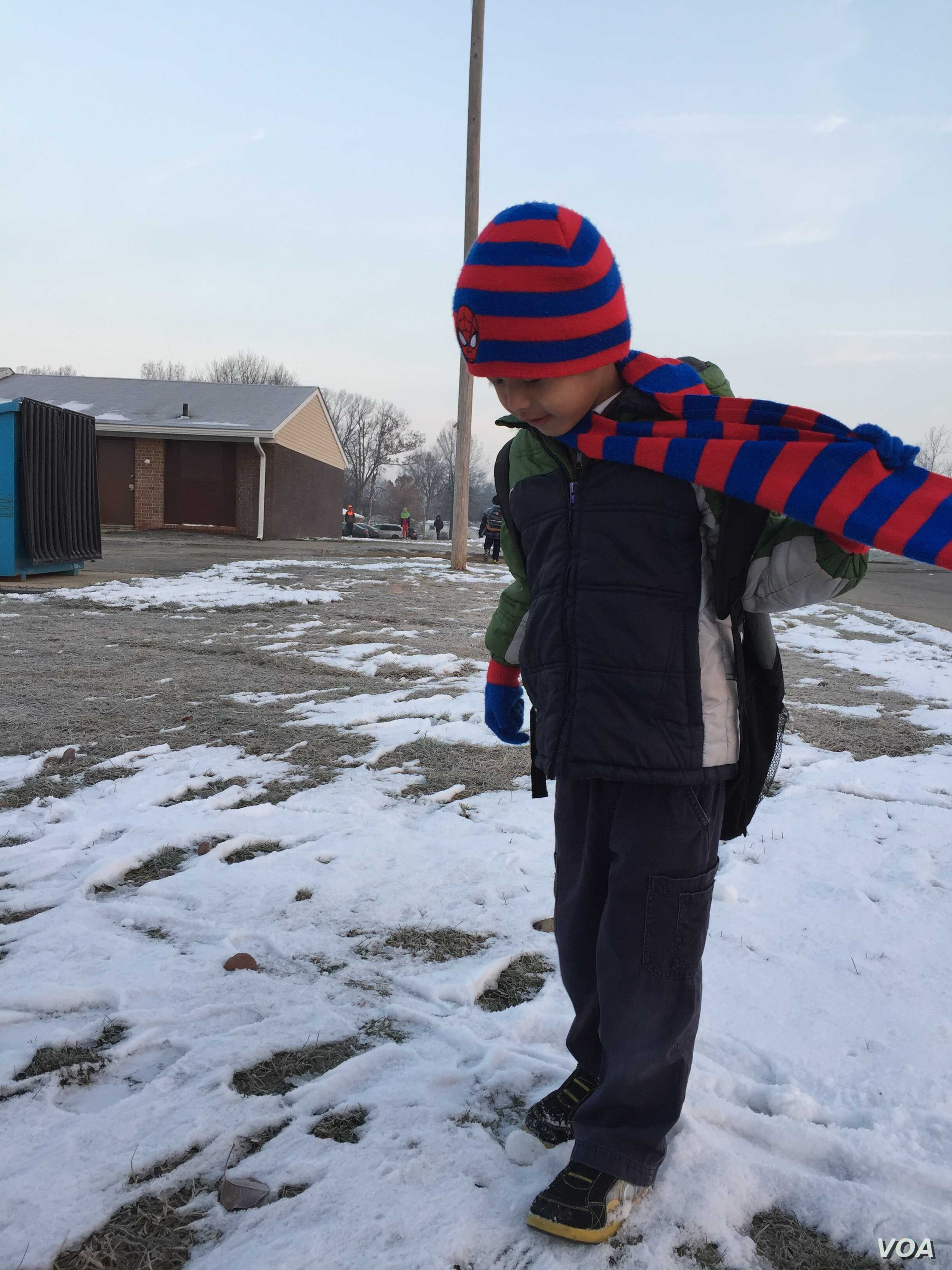Bu Say Wah waits for his school bus to pick him up. The first-grader is learning English as well as his native language at his Fort Wayne school. His teachers say he is a star pupil and respectful. (C. Presutti/VOA)