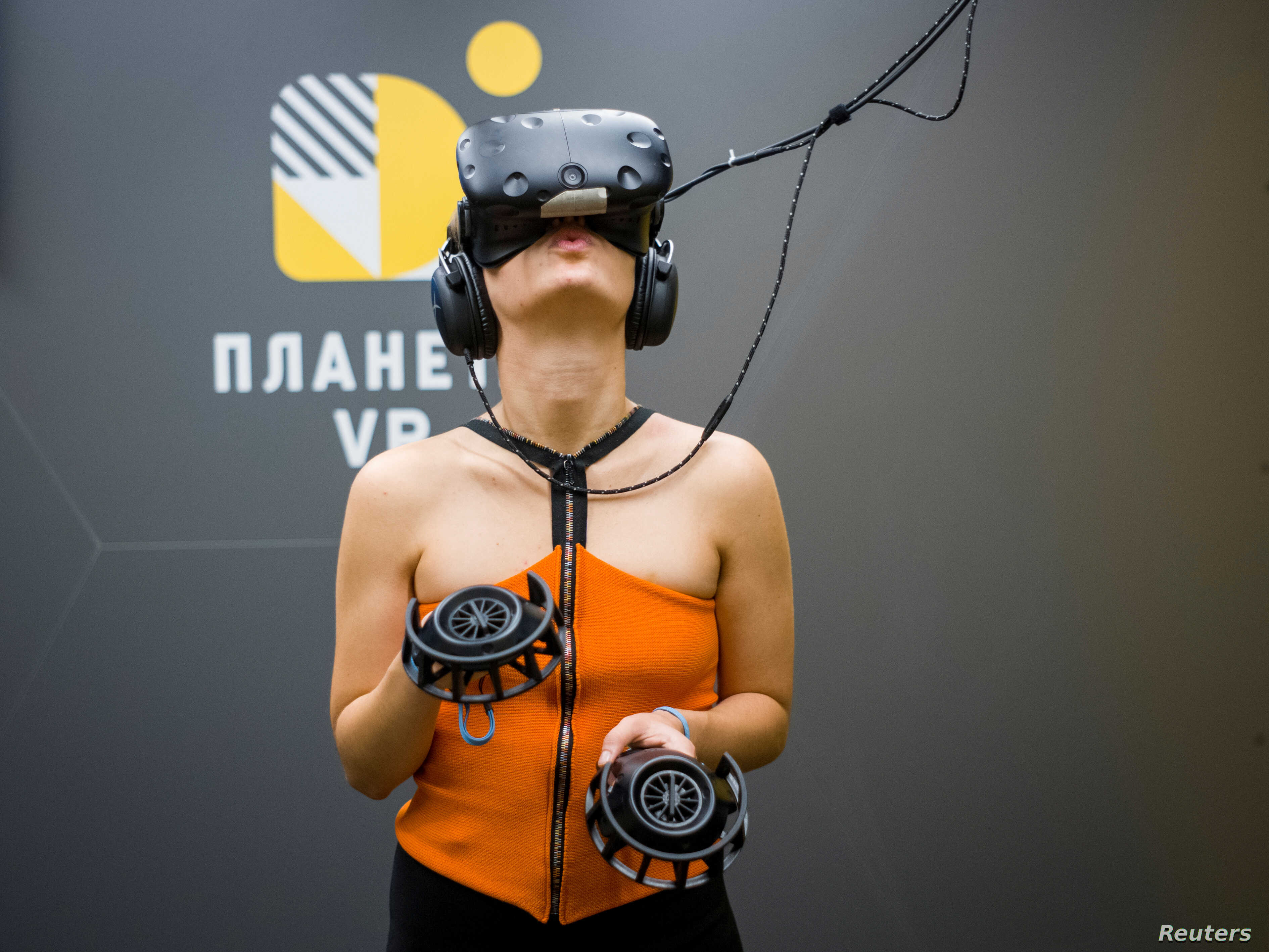 A visitor uses virtual reality glasses during the presentation of a simulator showing the 2013-14 demonstration in Ukraine, when dozens of protesters were killed in the final moments of Viktor Yanukovich's rule, in Kyiv, Ukraine Sept. 12, 2018.