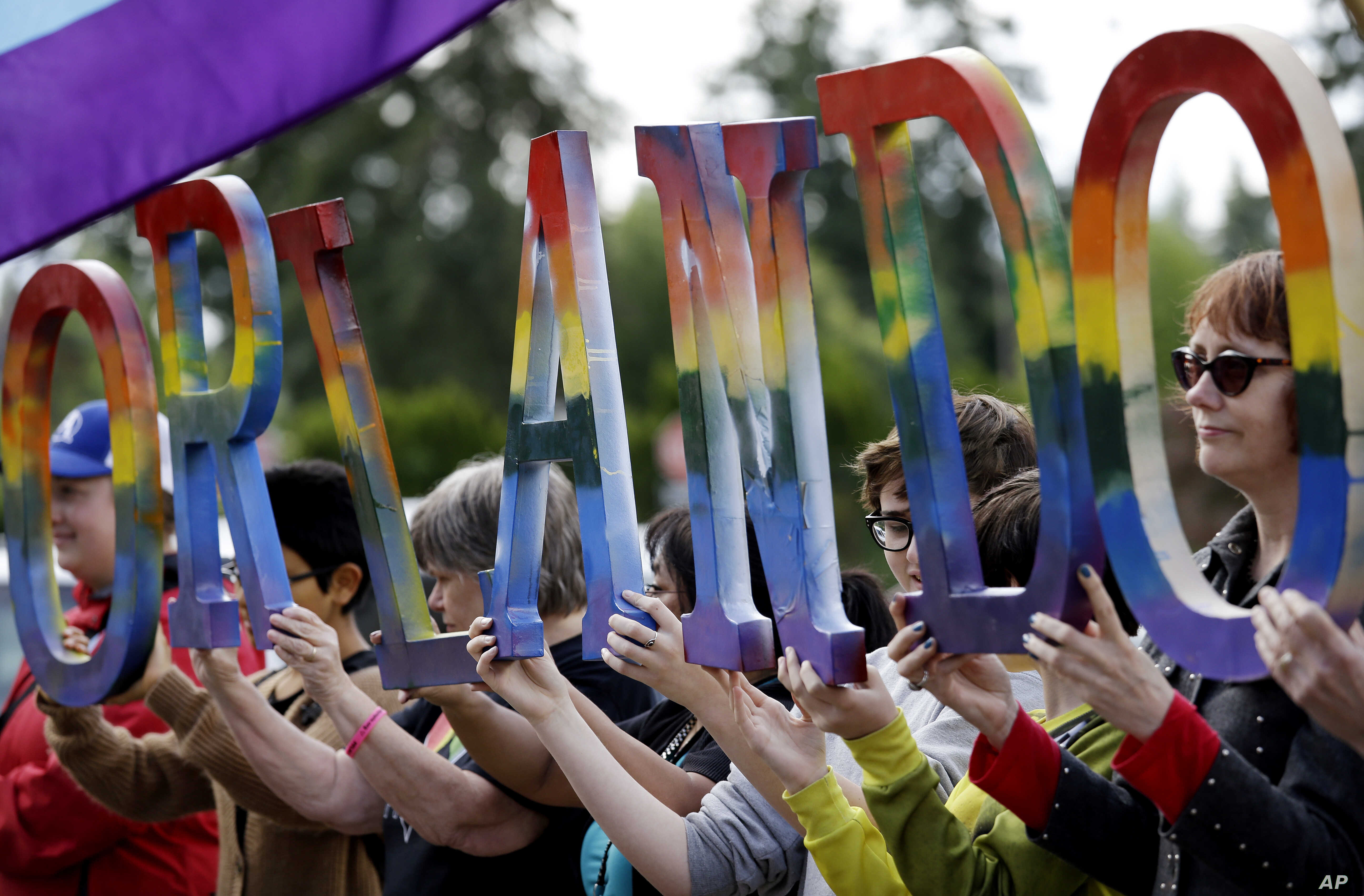 """Members of Capital City Pride and others from the LGBT community hold up letters spelling out """"Orlando"""" to honor of the recent shooting at a gay nightclub days earlier before the raising of a rainbow flag in front of the Washington state Capitol, Jun..."""