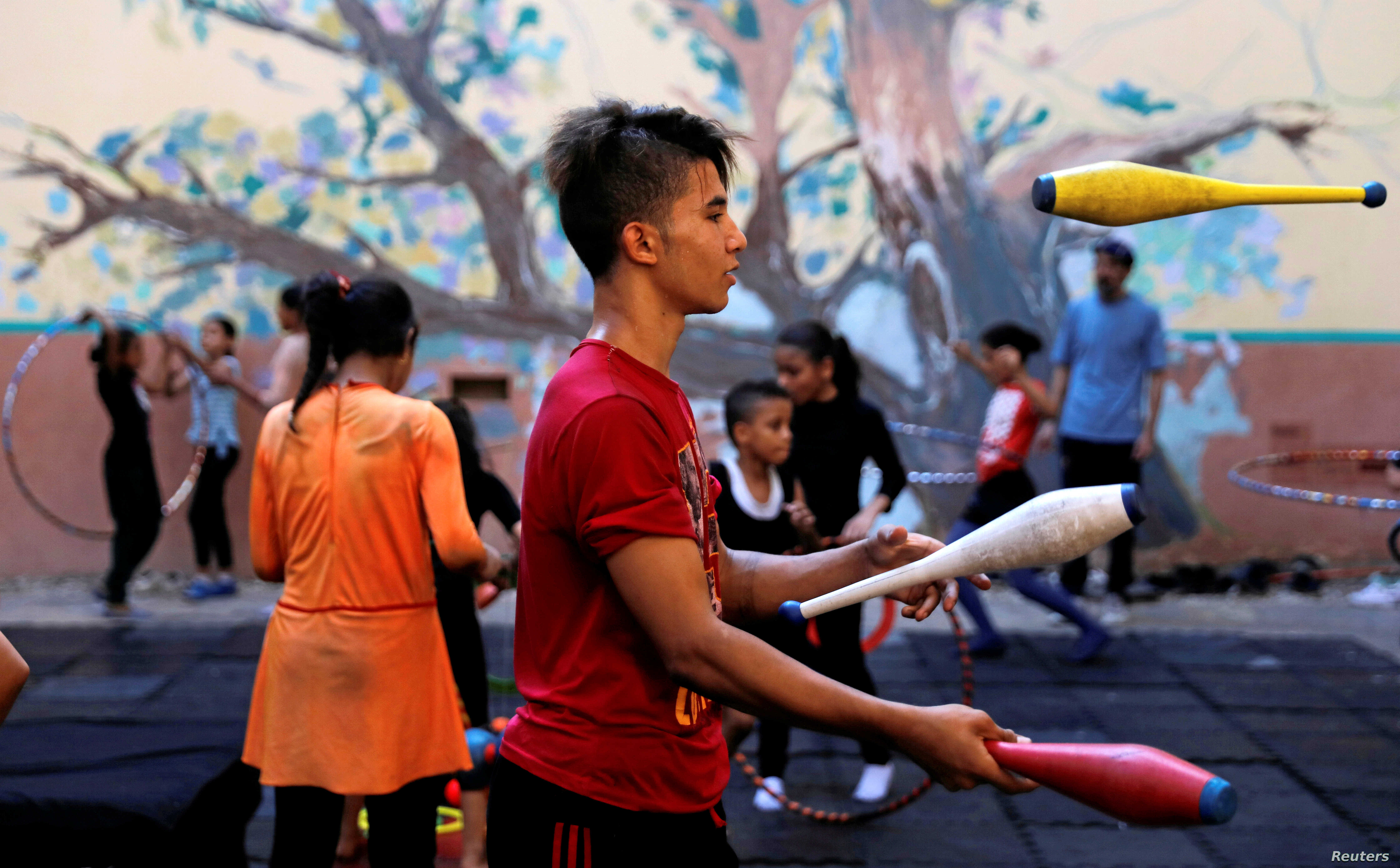 """A boy performs during a training session at al-Darb al-Ahmar Arts School """"DAAS"""" where children learn circus skills and arts in old Cairo, Egypt, July 17, 2018."""